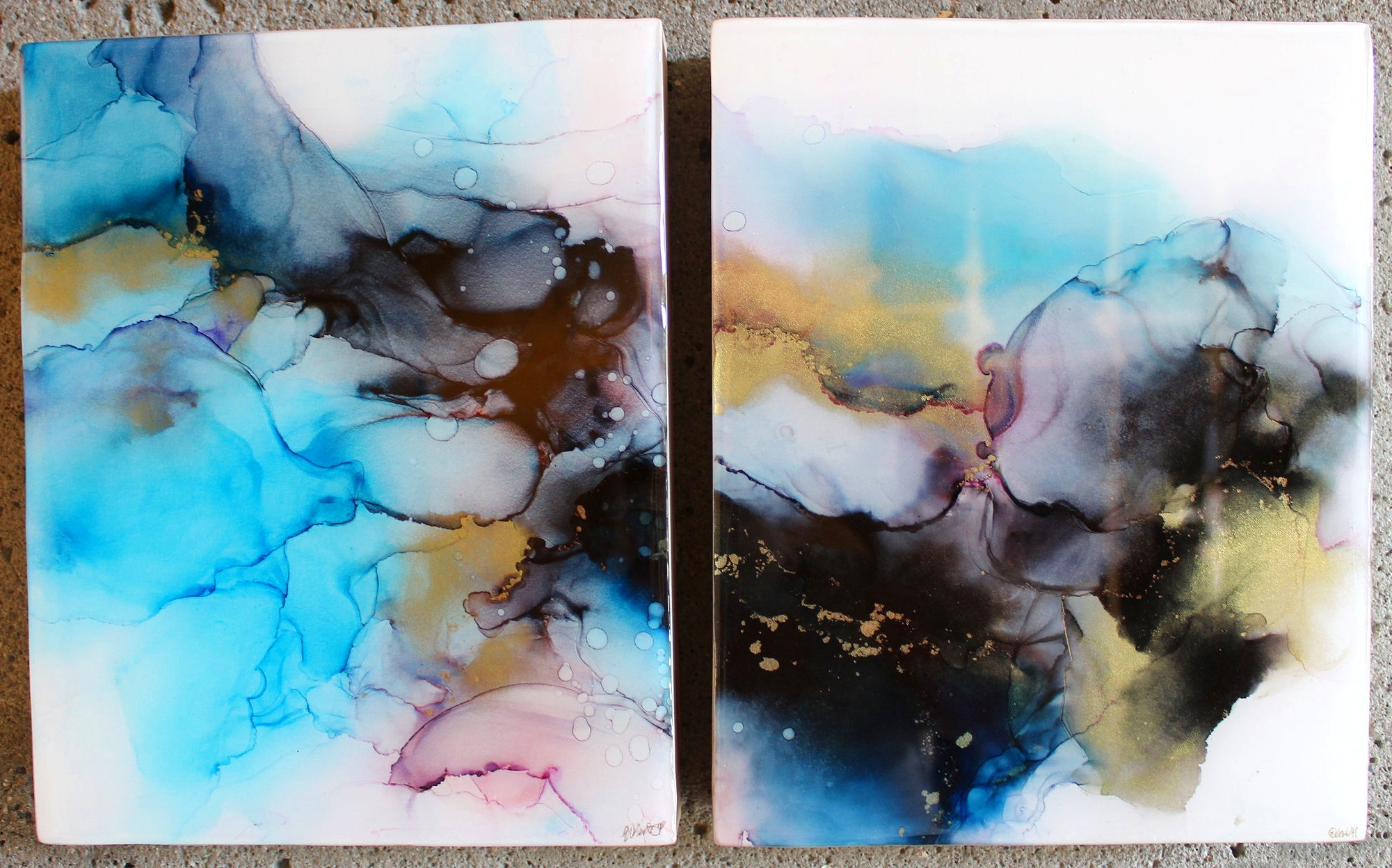 "Elizabeth Bate - Negative NebulaMy name is Liz and I am an alcohol ink artist here in Tacoma, WA. I discovered alcohol ink art several months back when I began to dabble in fluid art. I love how fluid, timeless and freeing inks can be. There are a variety of techniques and endless possibilities using this medium and you are not tied down to just one substrate to use as a canvas for your art. No two pieces are the same and the color combinations are endless.This piece is titled Negative Nebula. Negative nebula is an alcohol ink diptych made by adhering two pieces of synthetic paper called Yupo to 1 ½ cradled birch wood. I then used different drying techniques with alcohol ink and isopropyl to create my piece. After it has dried and been sealed, I then pour resin on top to give it a protective hard and shiny layer and really makes the colors pop. When you see pictures of nebulas you see them against the black vastness of the universe. My ""Negative Nebula"" is the response to that darkness in our galaxy. Different colors are immersing together against a white background to be a yin to the yang of our solar system."