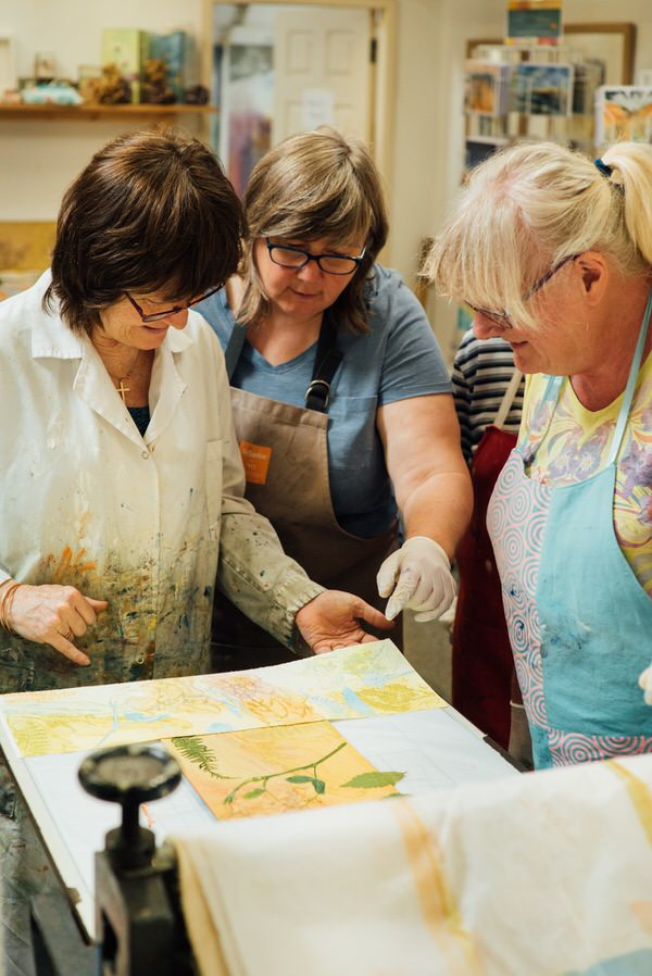 Carol and workshop students discussing a print
