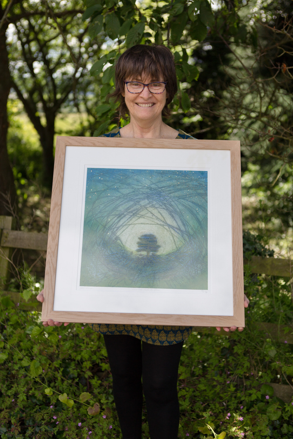 Carol Nunan holding one of her framed limited edition prints.