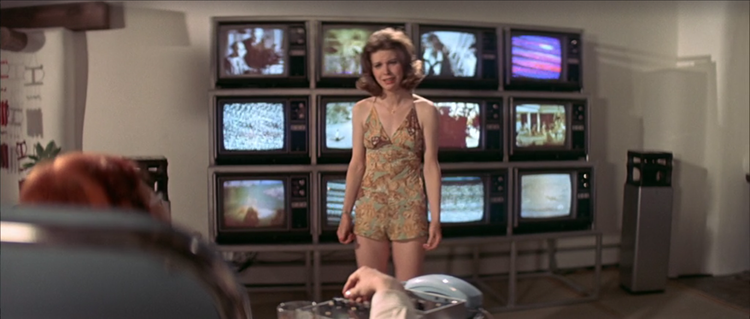 Candy Clark in  The Man Who Fell to Earth  (1976). Stacked televisions—here watched by David Bowie's character—quickly became an oft-used visual metaphor for overconsumption.