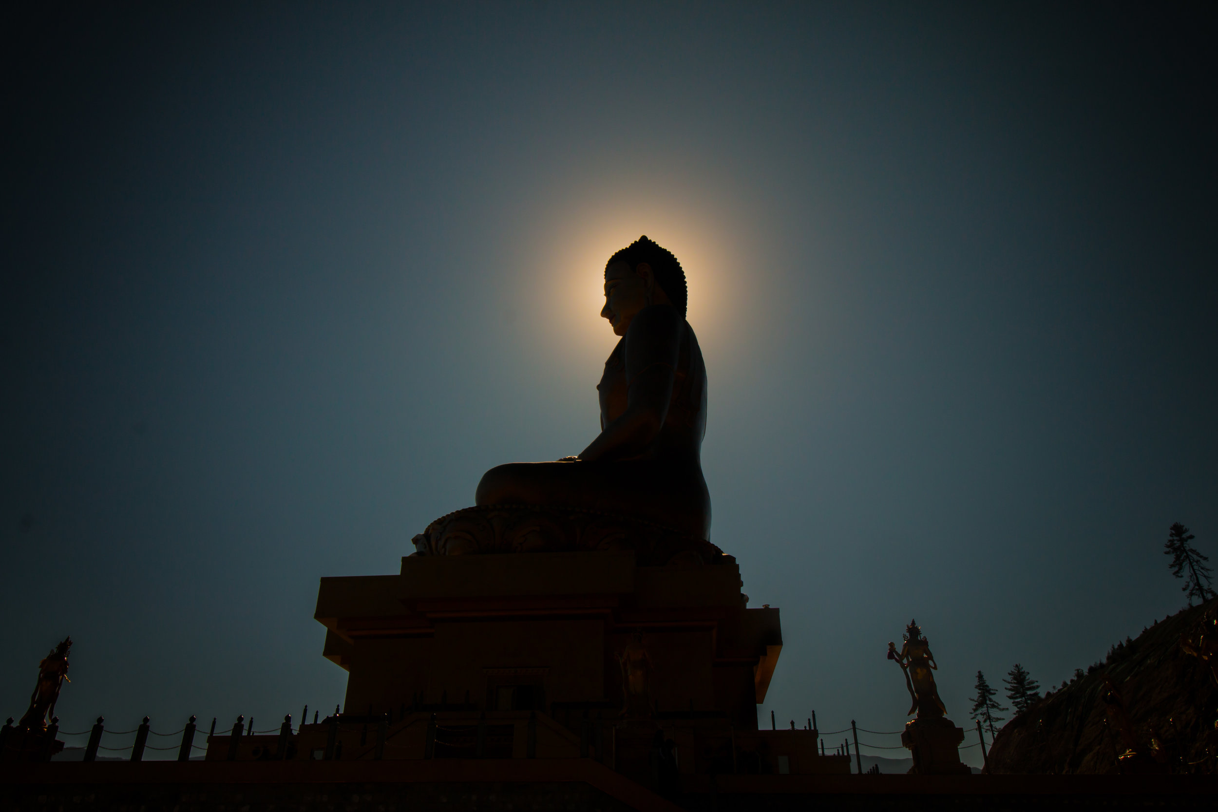 Buddha silhouetted by the moon