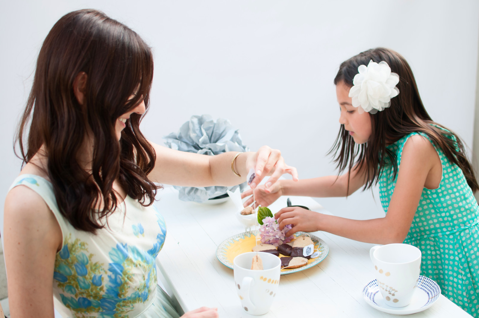 Preparing the plate of tea cookies and the table with flowers and our DIY tea cups.