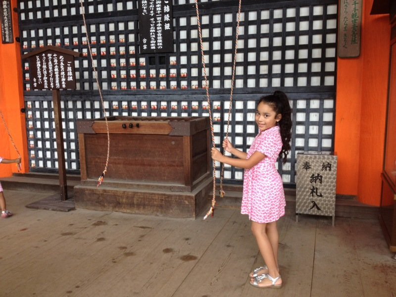Mia pulls on the ropes to ring the temple bells