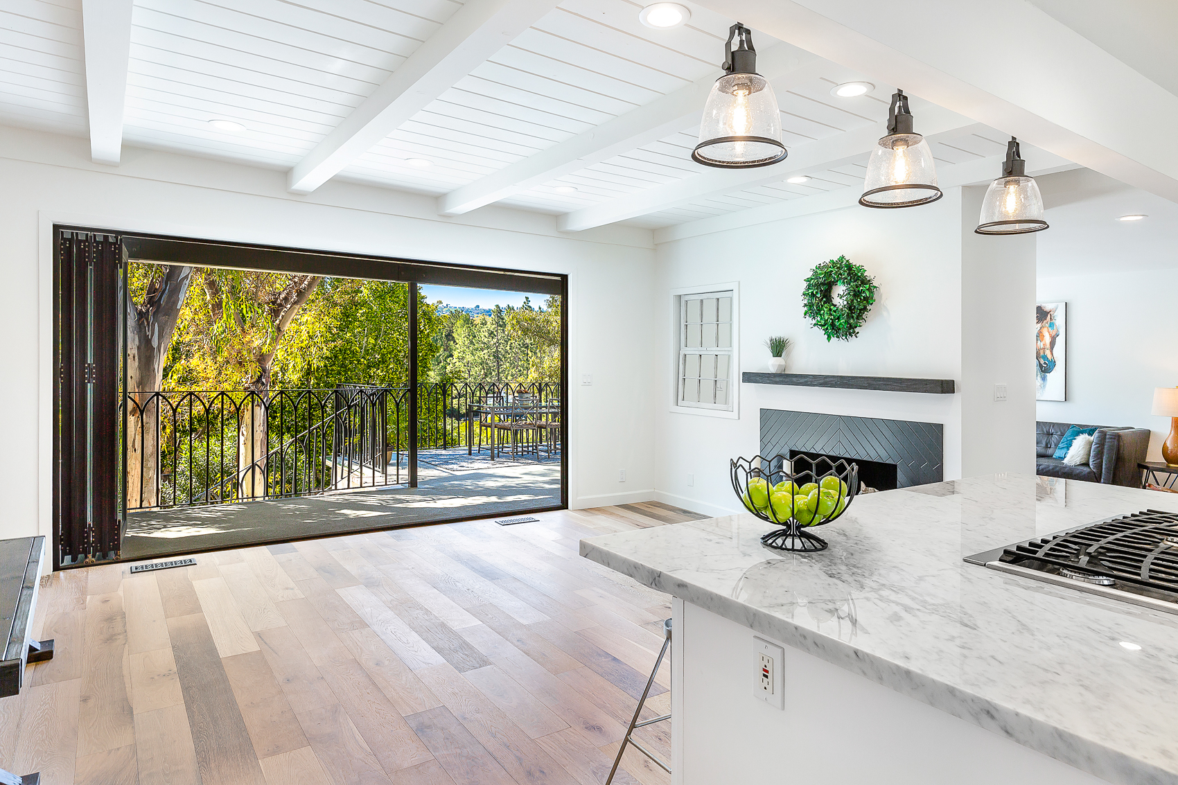 Panoramic folding doors create an indoor/outdoor flow that is the pinnacle of SoCal living. And the custom wrought iron modern farmhouse railing adds a dramatic backdrop to your dining experience.
