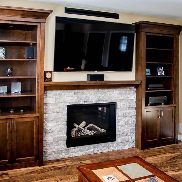 Custom built-in wall unit and mantle that even has blanket storage!! #customcabinets #wallunit #fireplace #mantle #livingroomdesign