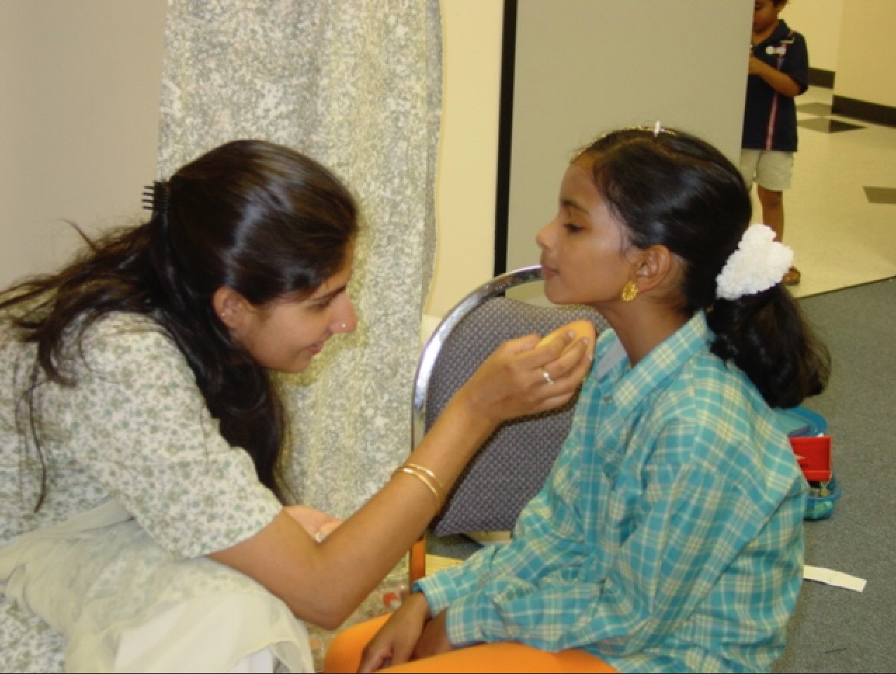 Lavanya helps a young dancer get stage ready for Silambam's student showcase in 2006