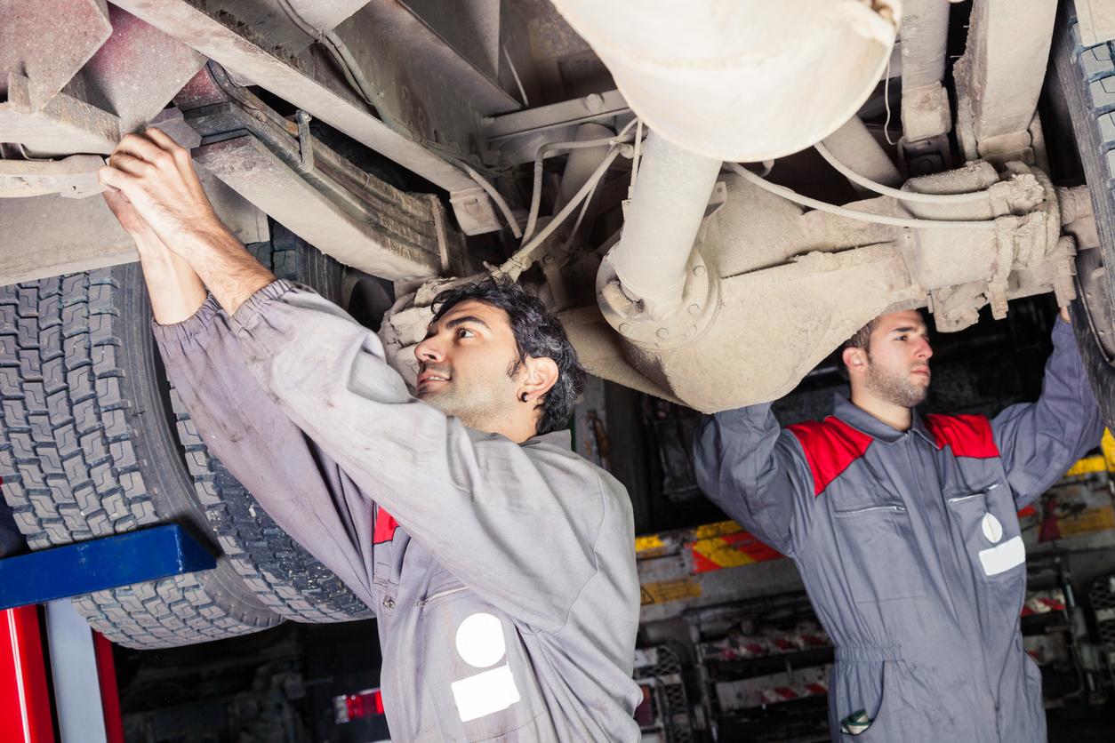 Mechanics inspecting a truck for maintenance.