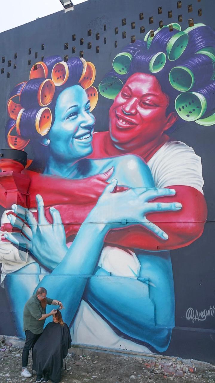 DFAM Board Member Nicholas Mason cutting hair in Santurce, Puerto Rico  Mural by Evaristo Angurria