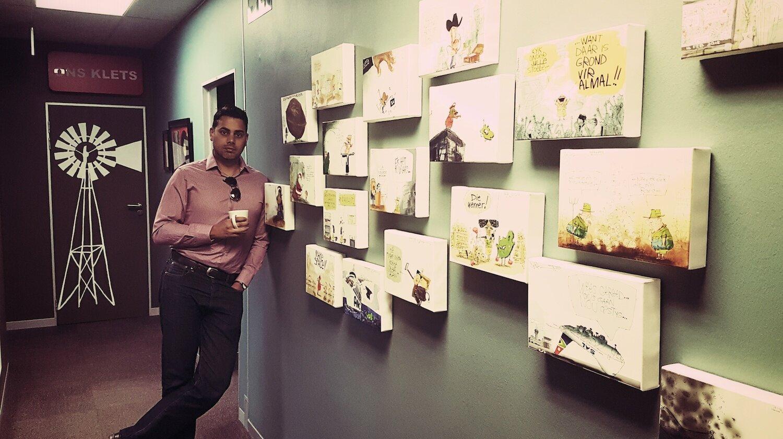 Jerm alongside a wall of his work at Maroela Media.