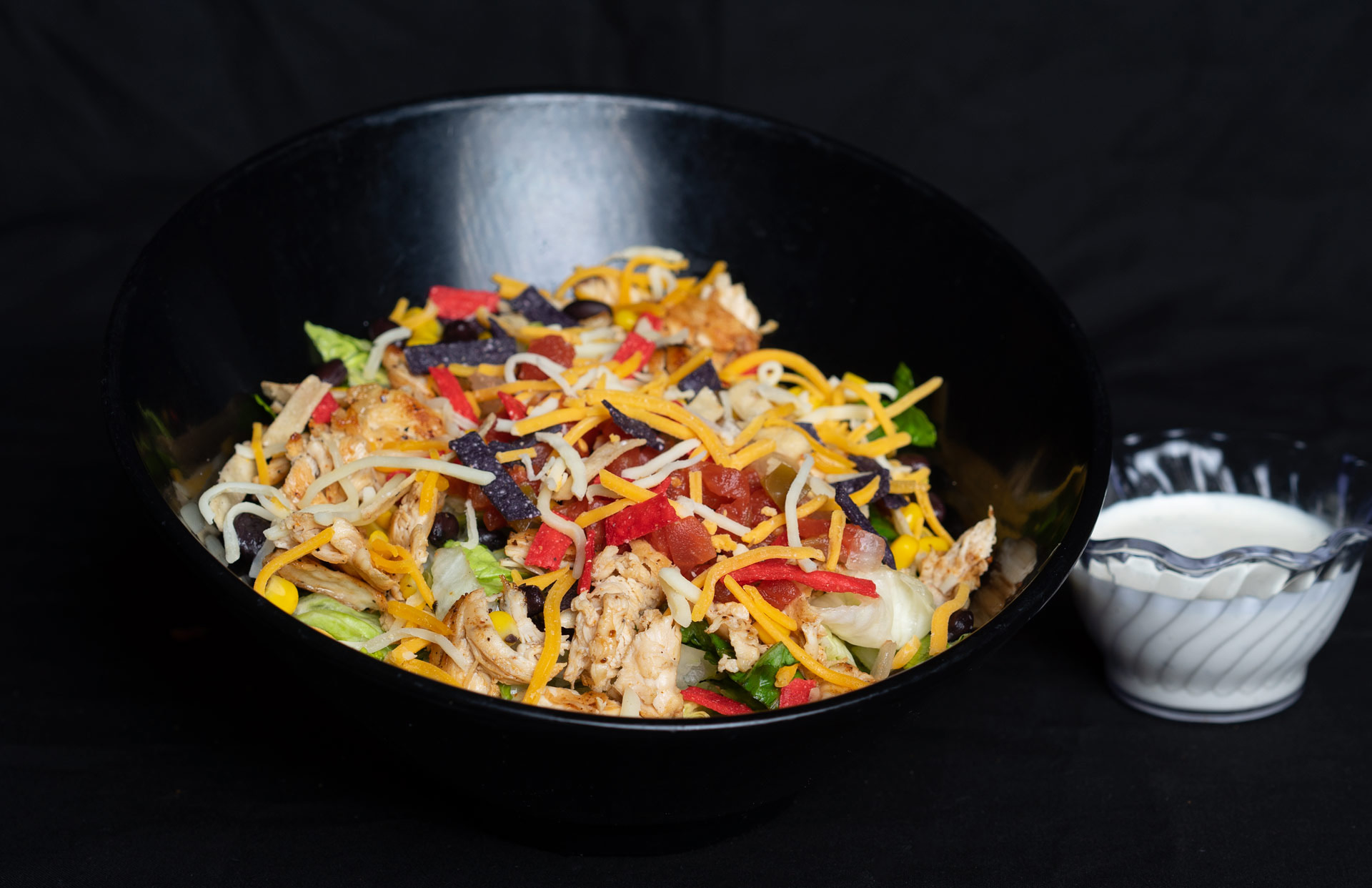 Southwest Chicken Salad Fresh mixed greens topped with fajita grilled chicken breast, black bean corn relish, Pico de Gallo, cheddar jack cheese, and tortilla strips. Served with a side of jalapeno ranch dressing. 12.00