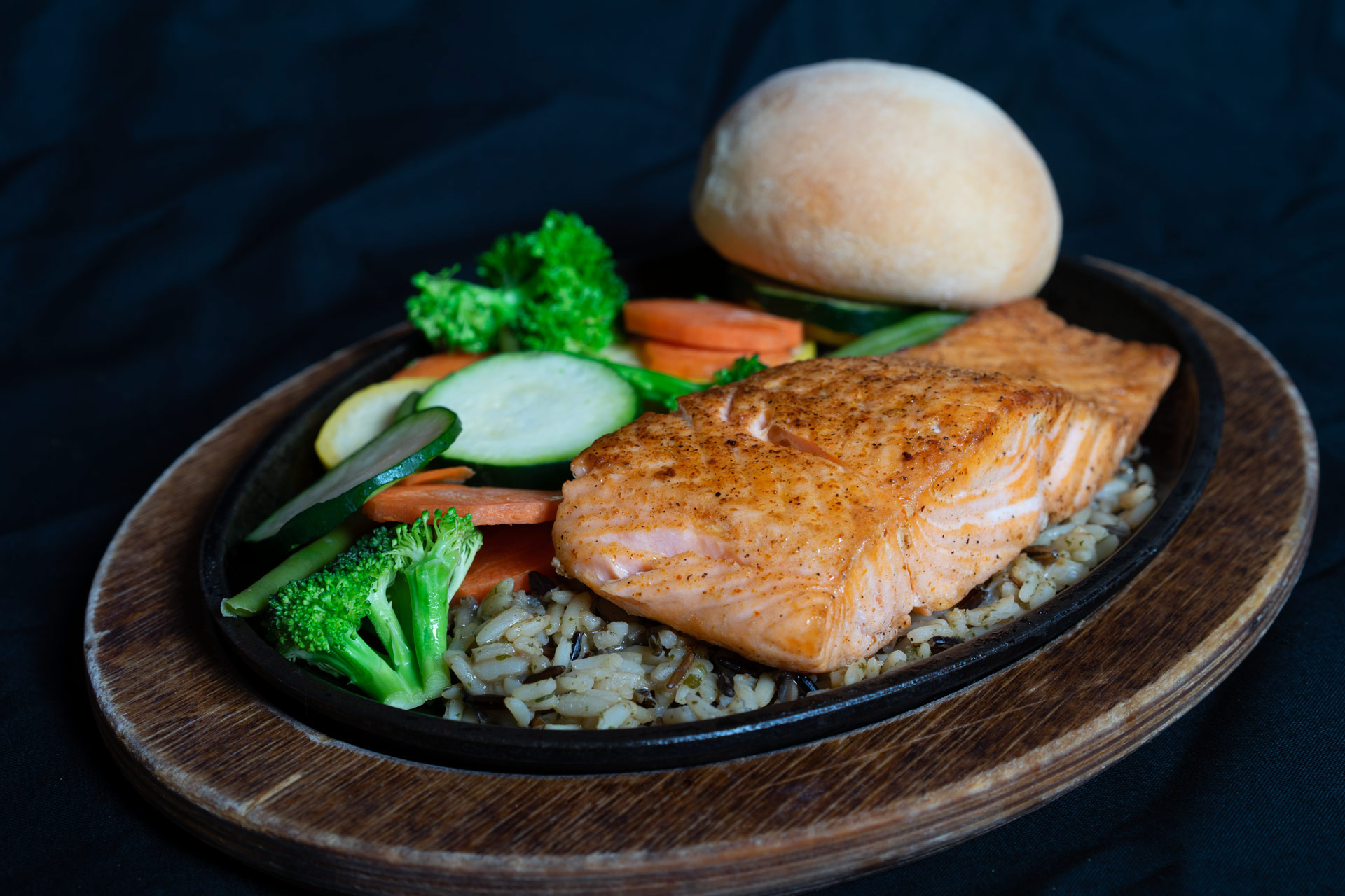 Grilled Atlantic Salmon 8 oz. serving of Norwegian Salmon seasoned, grilled and served over a bed of wild rice. Accompanied by your choice of steamed or grilled fresh vegetables and a house prepared yeast roll. 15.00