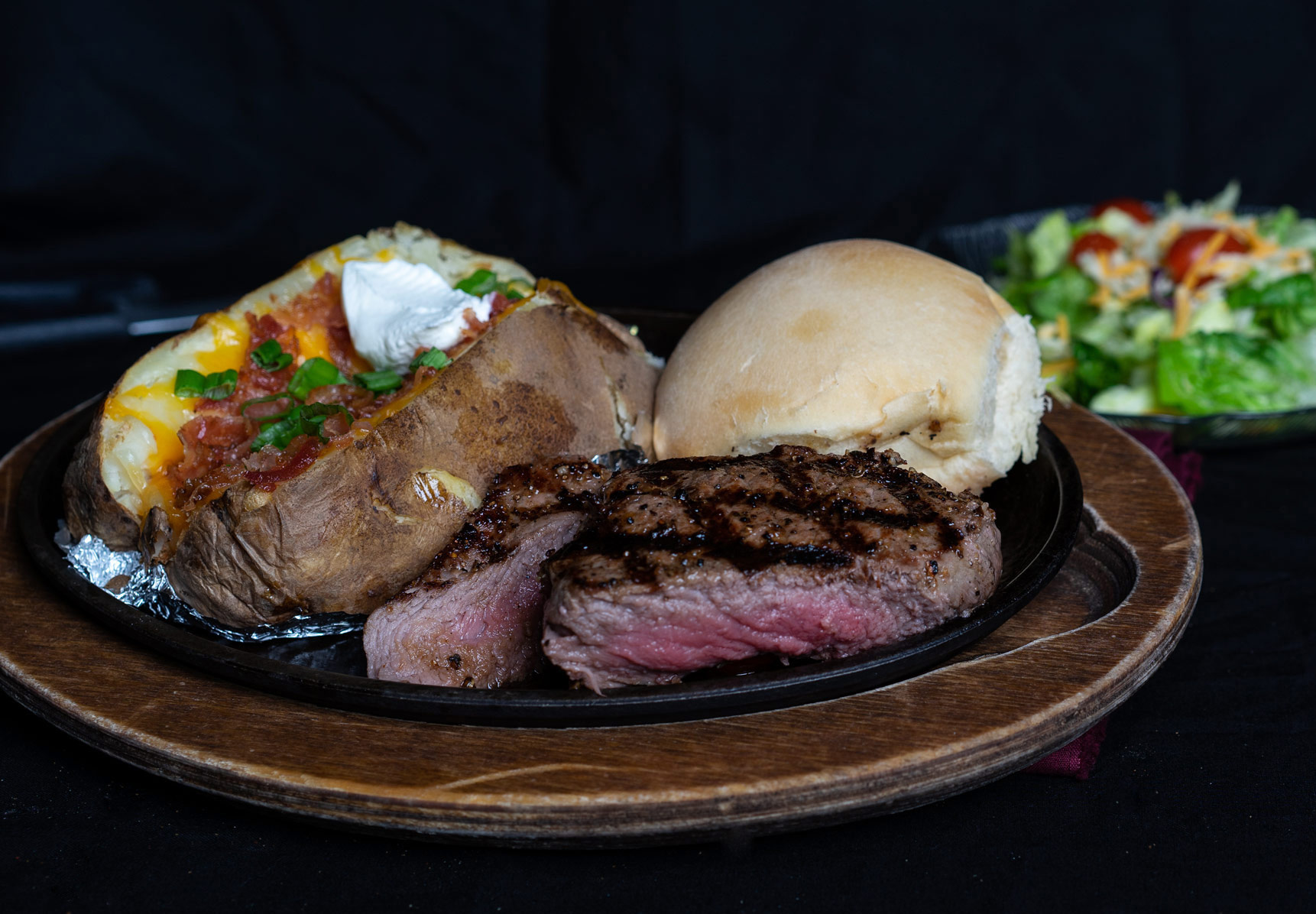 Top Sirloin Steak An eight ounce serving of naturally lean  1855 Certified Black Angus Beef  carved from the center of the sirloin to give it a bold, beefy flavor. Accompanied with baked potato, house prepared yeast roll and salad bar. 17.00