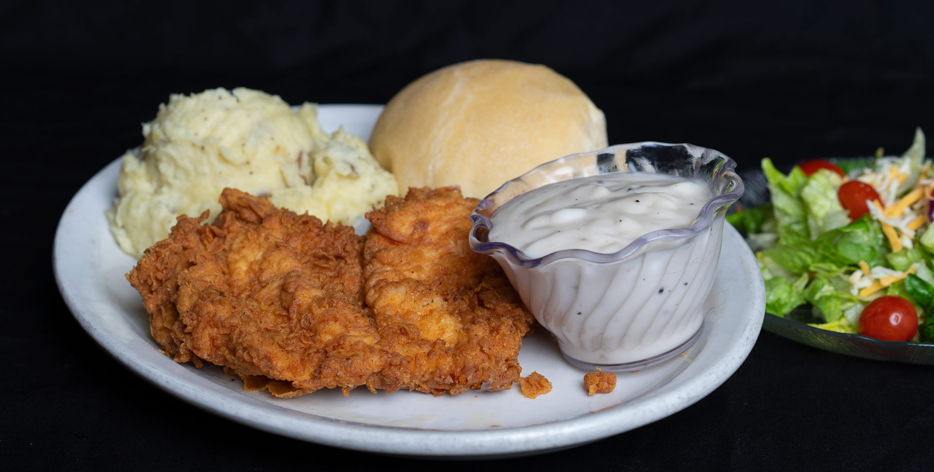 Chicken Fried Chicken 8 oz. boneless chicken breast fried to a golden brown. Served with country or brown gravy on the side with baked or mashed potatoes and an in-house prepared yeast roll. 12.00