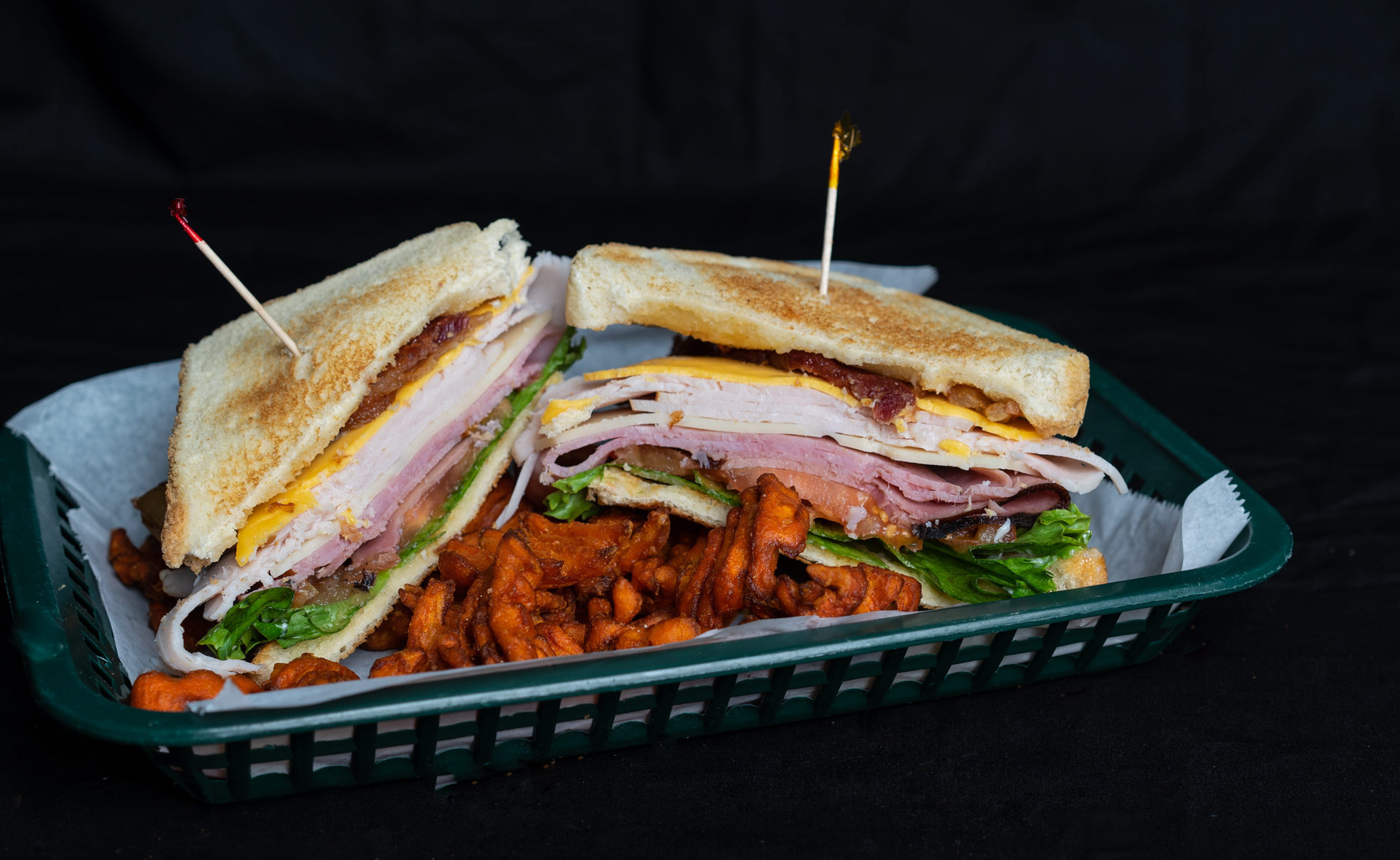 Mack's Club Sandwich Mountains of deli ham and turkey accented with crispy bacon, tomato, lettuce and cheese on Texas Toast. Served with your choice of steak fries, french fries, onion rings, chips, or Texas Toothpicks. 8.00