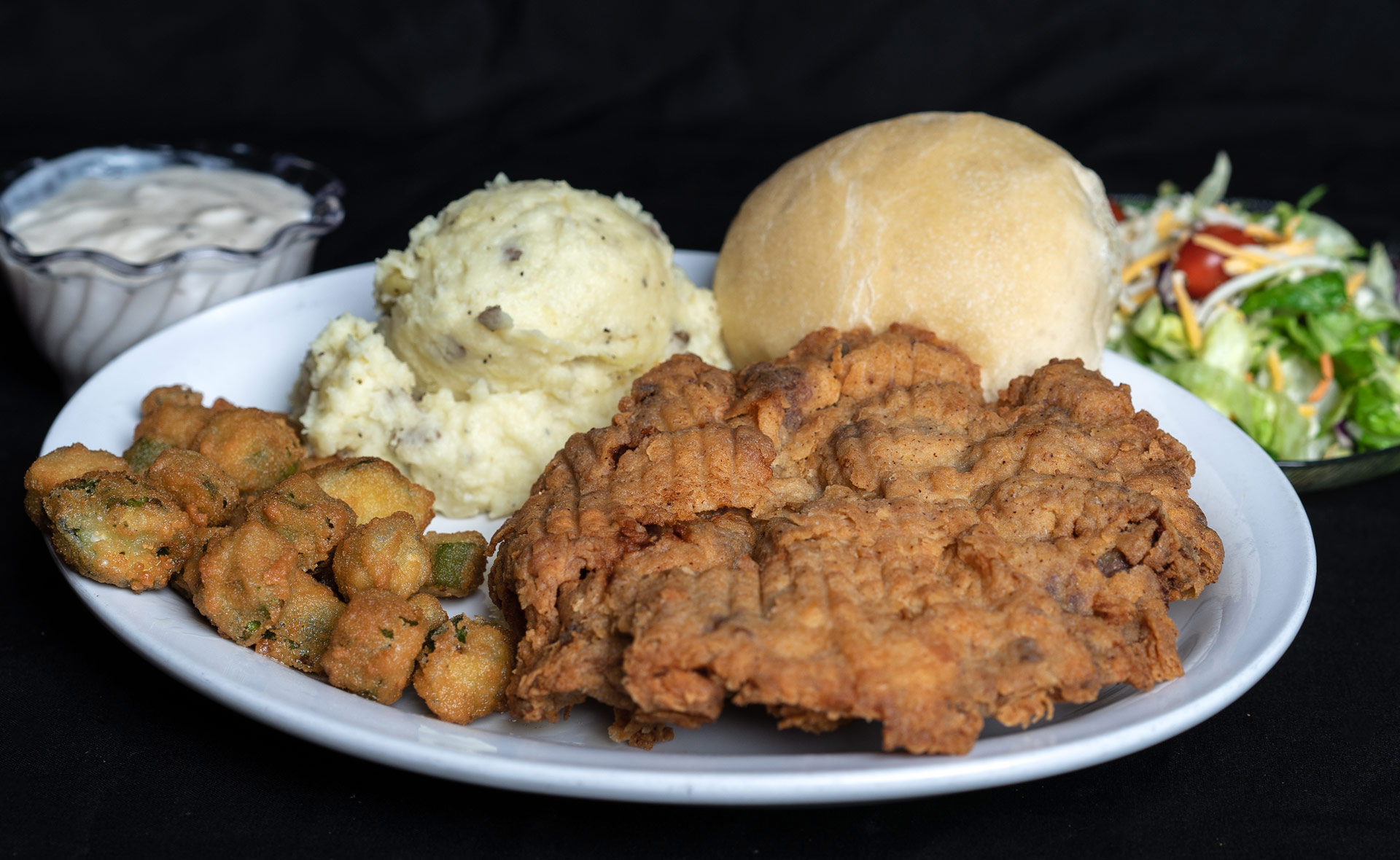 Chicken Fried Steak 8 oz. beef cutlet deep fried to a golden brown. Served with country or brown gravy on the side with baked or mashed potatoes, fried okra, salad bar and an in-house prepared yeast roll. 15.00