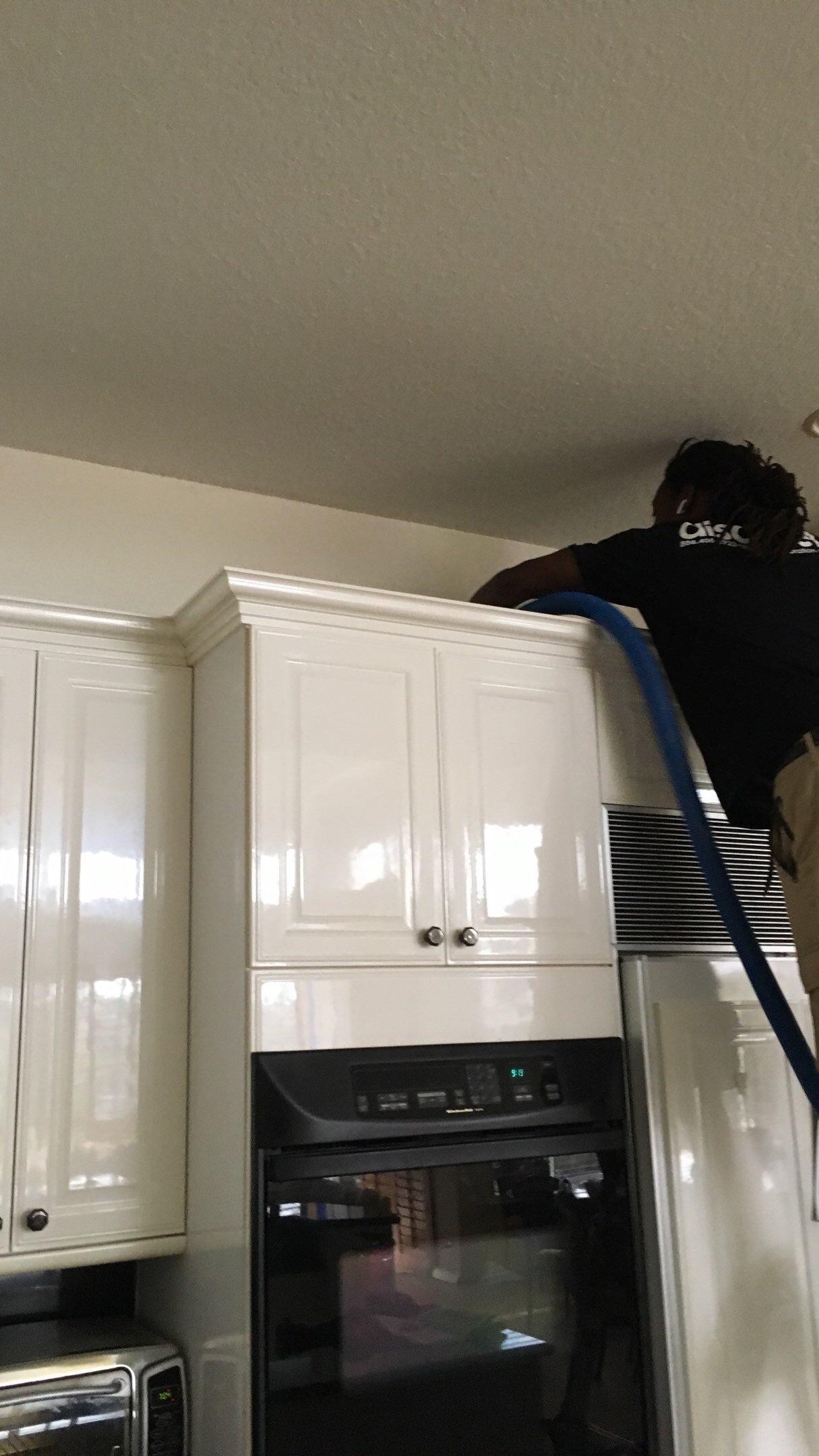 technician hepa-vacuuming kitchen cabinets