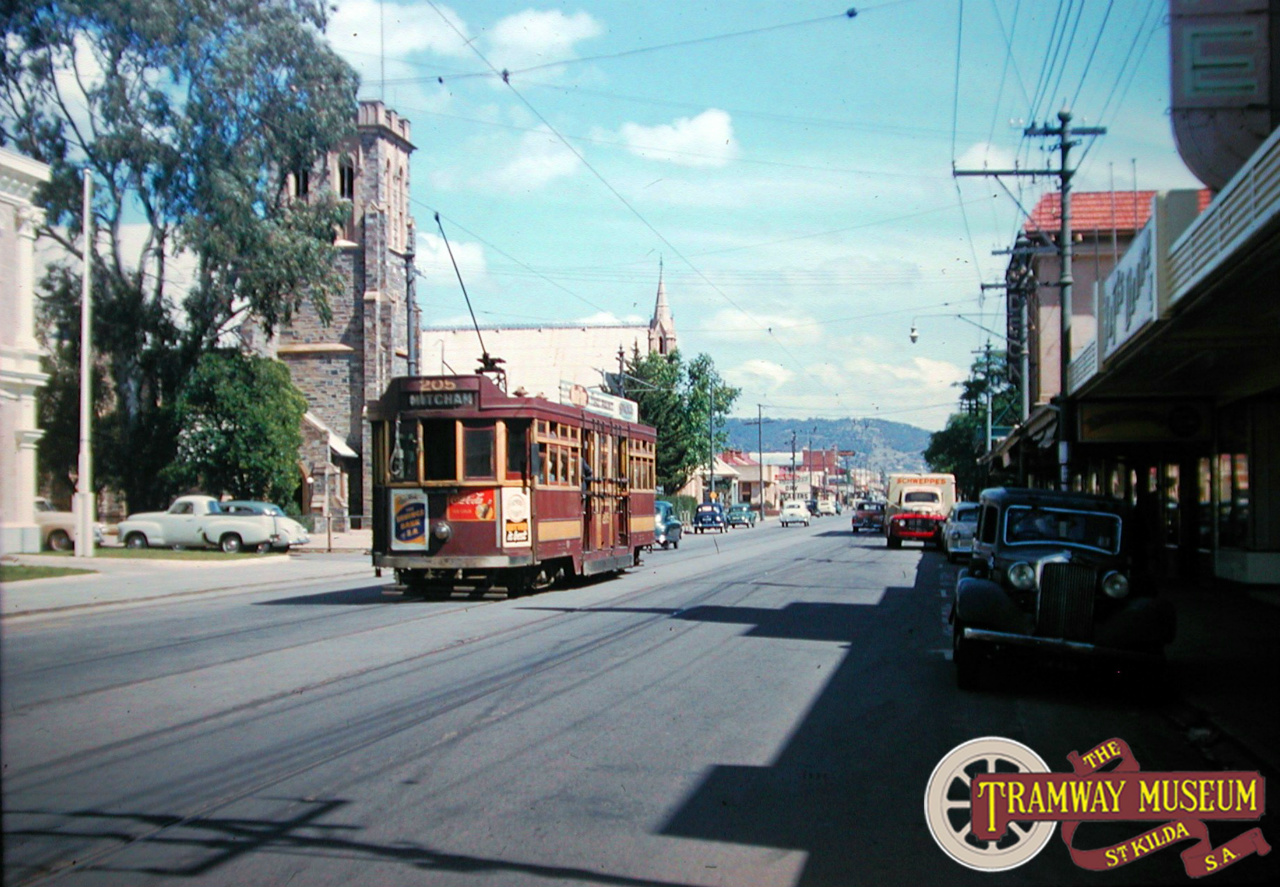 'Drop Centre' tram 205 is seen here in Unley Road heading towards Mitcham in the mid 1950s. Some elements of this scene have remained the same since the trams ceased running on Unley Road with the two churches on the left of the road still standing. The present day Coles Supermarket would be where the local shops are on the right of this shot. Photo: Keith Kings.