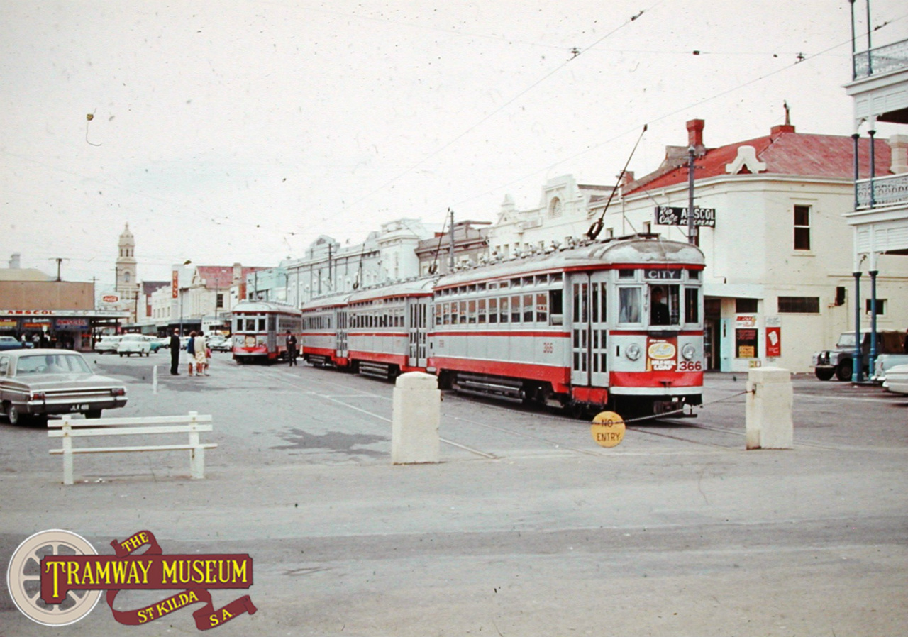 In 1967, a recreation of the three car 'sets' of trams was run with the special convoy seen here at Moseley Square in Glenelg. After the opening of the Glenelg line in 1929 until a serious accident in 1937 which stopped the practice, three car sets of H type trams were seen in peak hours on the Glenelg line. A regular service to the City can be seen arriving on the second track provided at this terminus. Photo: Barry Marshall.