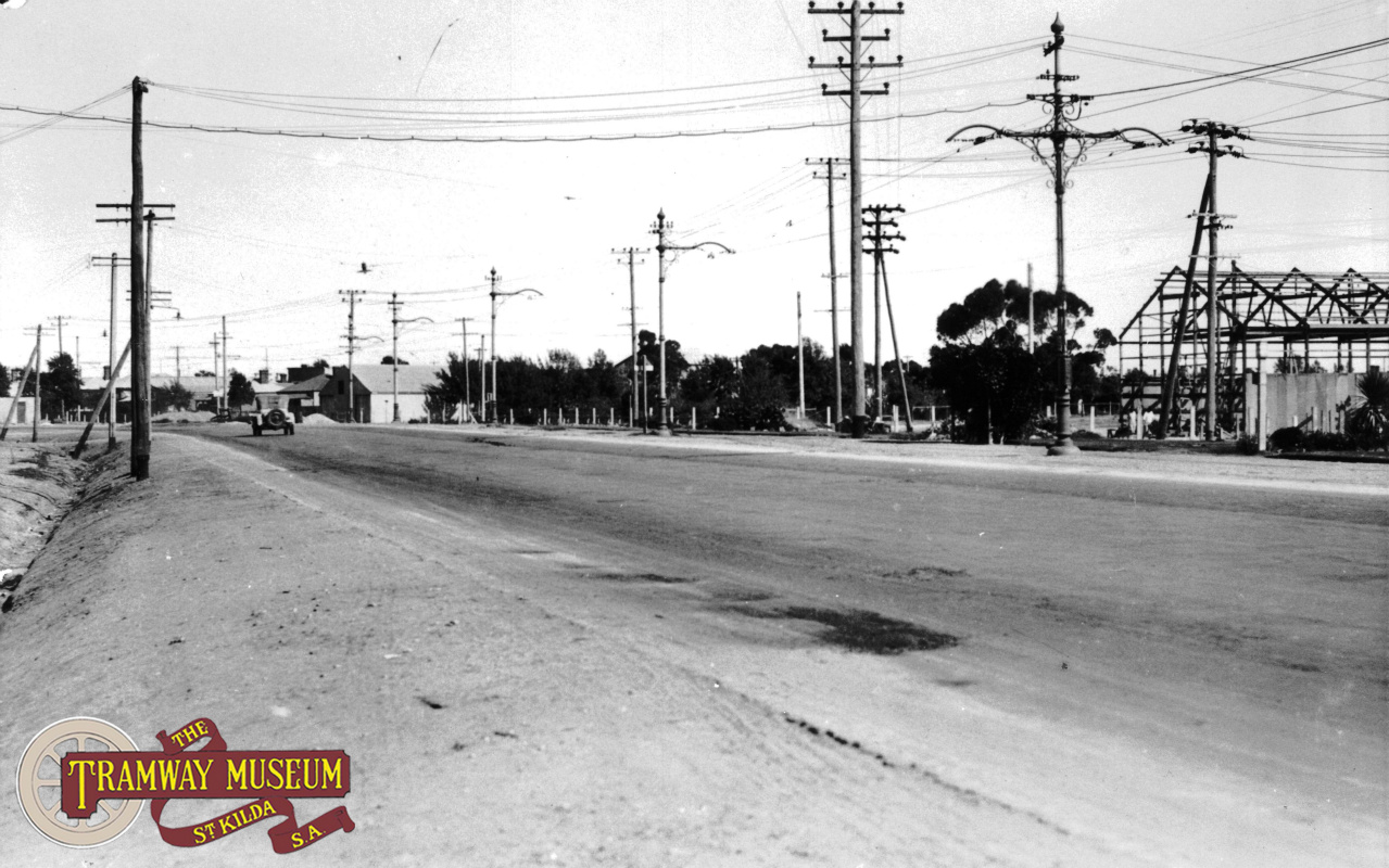The line to Albert Park ran on the eastern side of the generous expanse of the Port Road median strip and was single track after leaving the Commercial Road precinct. In this photo, the overhead poles show the point where the double track section ended in Port Road. The Port Adelaide depot is out of frame to the left.
