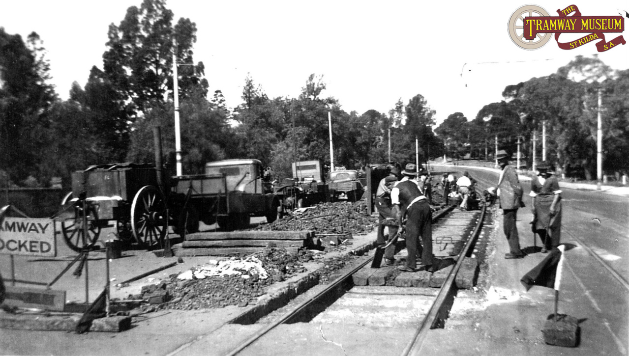 When the rails in the tramway finally became too worn to use, the track gang would dig up the road surface and replace the rails. Seen here in 1942 near the Botanic Gardens on North Terrace, the track gang have already removed the old rails and are putting the replacement sections in. Photo: MTT.