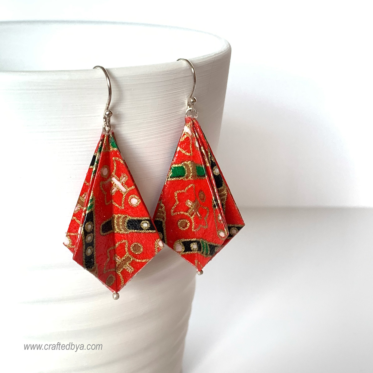- Origami earringsMade with Japanese Yuzen handmade paper and sterling silver findingsEvery pair is hand folded and therefore uniqueCoated with a non-toxic sealant for durability and water resistance
