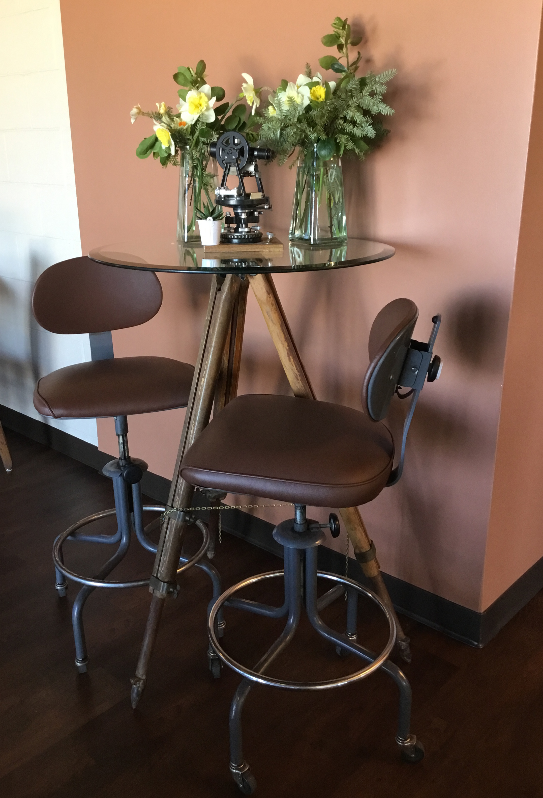 This former survey mid-1900's transit was paired with an early 1900's wooden tripod and a new glass table top to create a cocktail table. The mid-century drafting stools were recovered. -