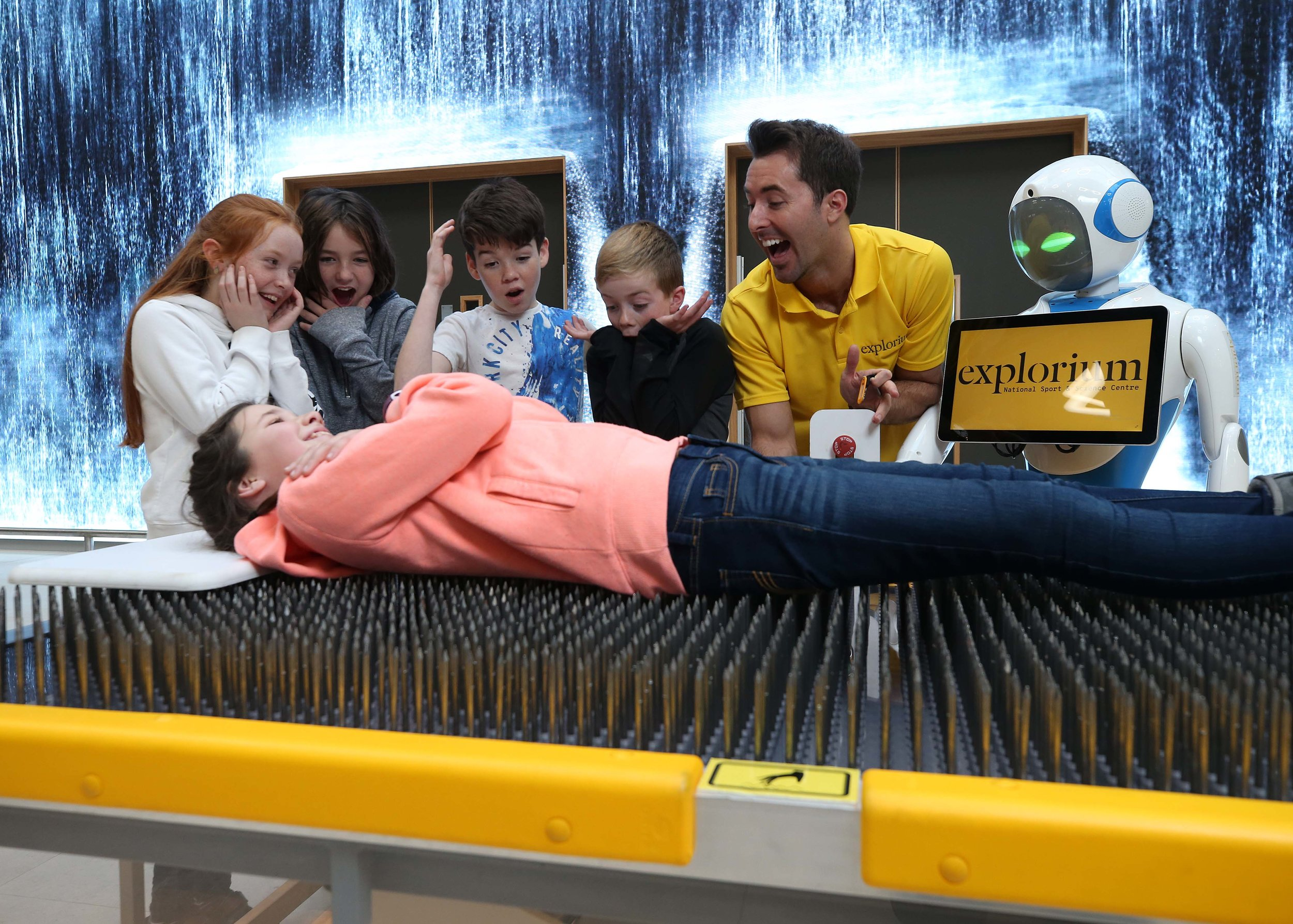 Explorium Bed of nails exhibit with Mark Langtry, kids and robot.JPG