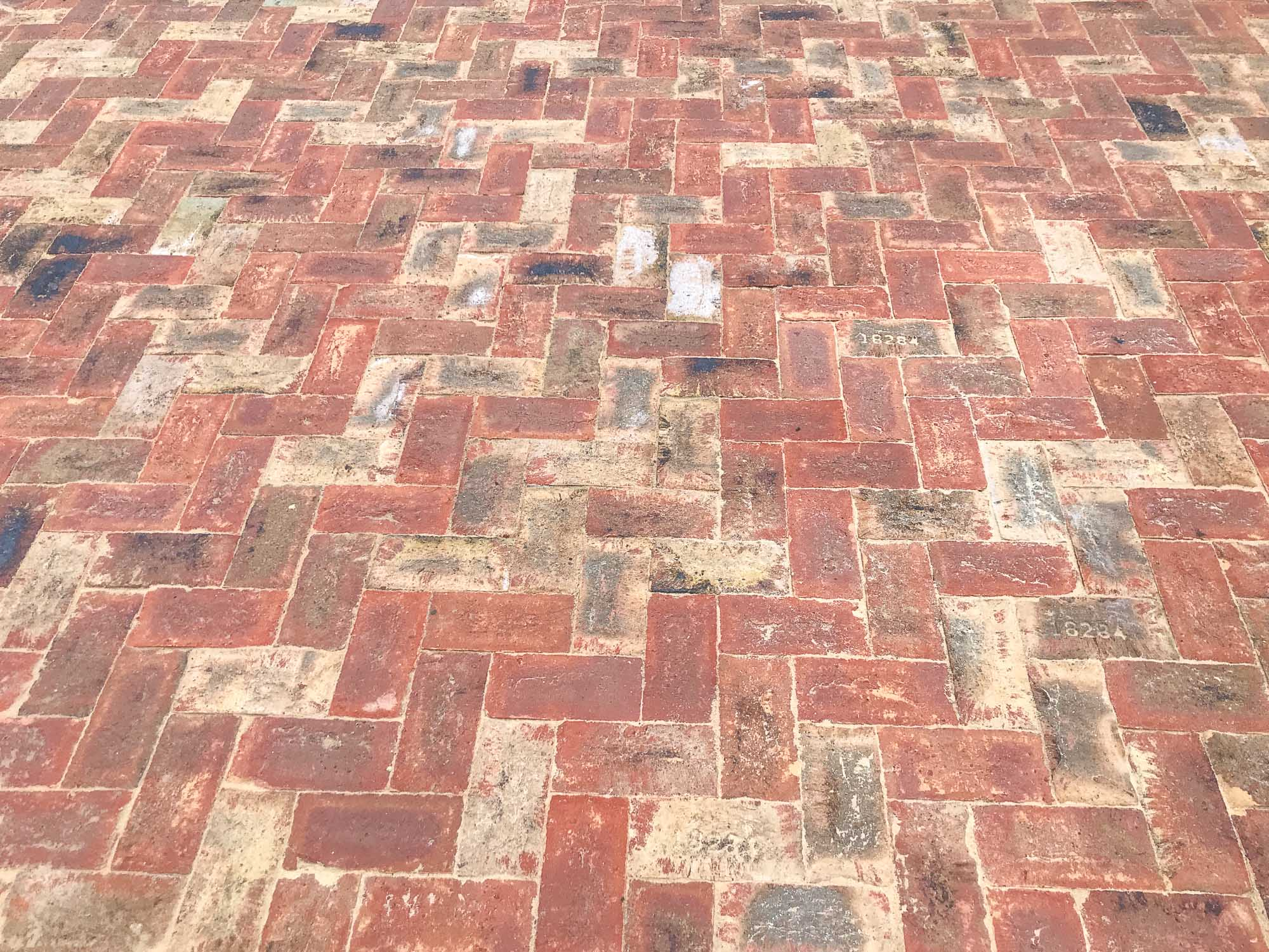 The mix of red, buff and black/blue colours in this brick patio creates a mottled pattern which is a far cry from the rather stark appearance of modern paving setts
