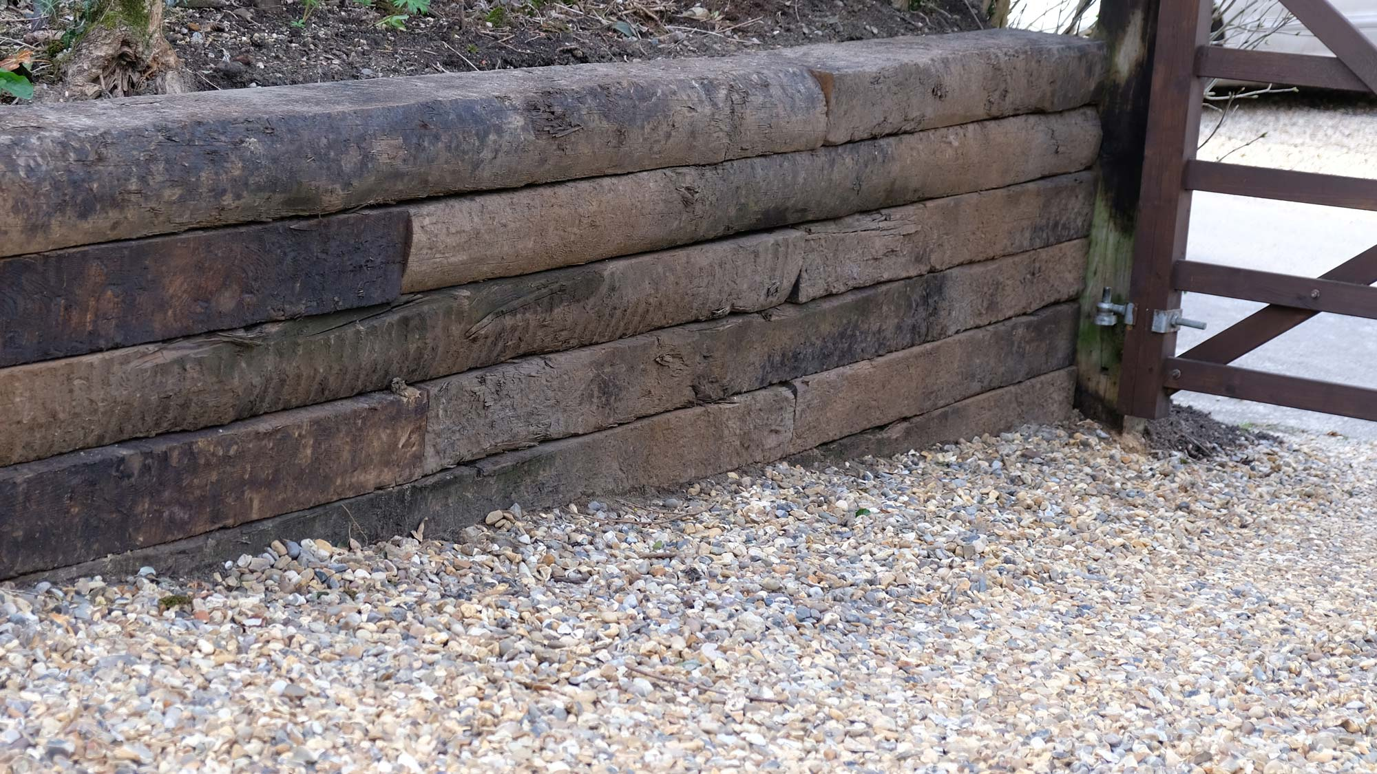 Reclaimed railway sleepers make a low-key and economical retaining wall