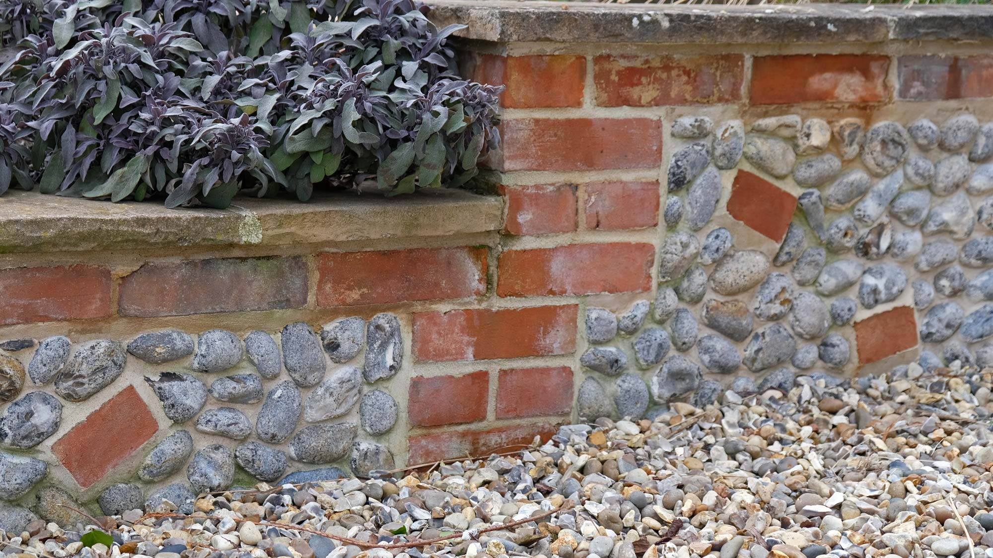 A low brick and flint retaining wall is ideal for plants (in this case a purple-leaved sage) to flop over