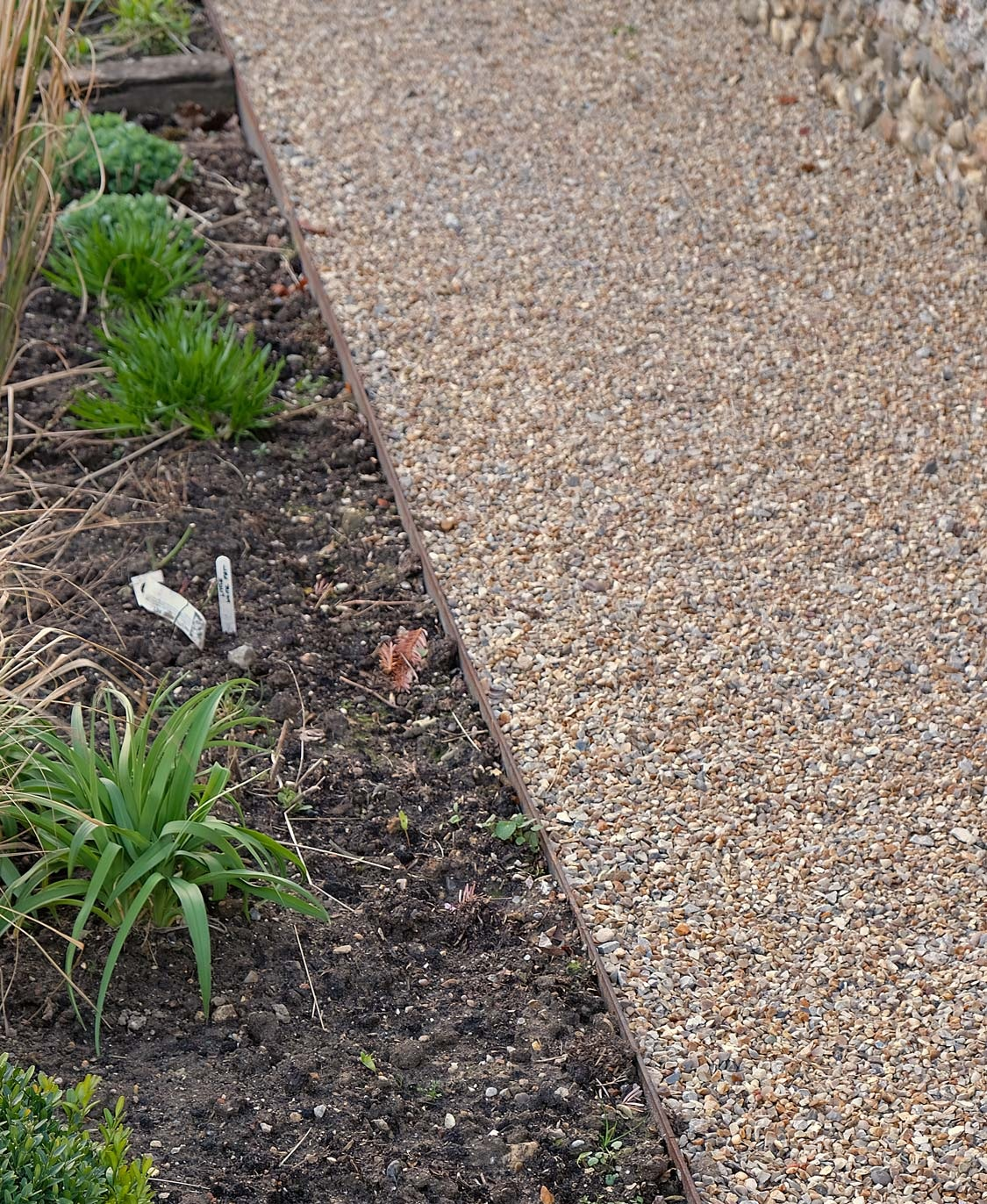Metal edging is best when a more-or-less invisible transition is required - and it can be bent into curves!