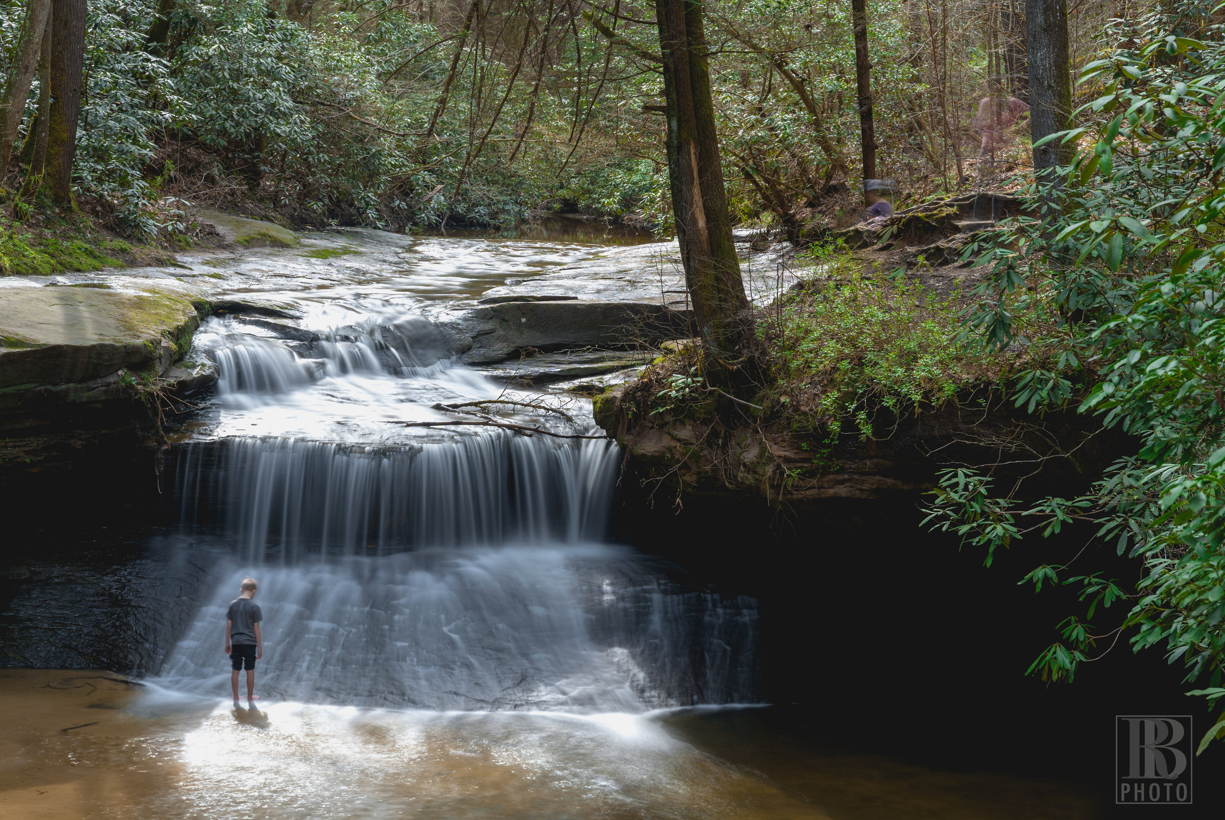 In order to smooth out the waterfalls, I use a neutral density filter and a long exposure… 23 seconds in this case. The added benefit of doing that is that as people move in or out of the frame they generally don't show up in the final image, or if they do it's faint enough that they're super easy to Photoshop out. This little dude stood stock-still for the entire 23 second exposure and actually turned out to provide a really cool element to the final image.