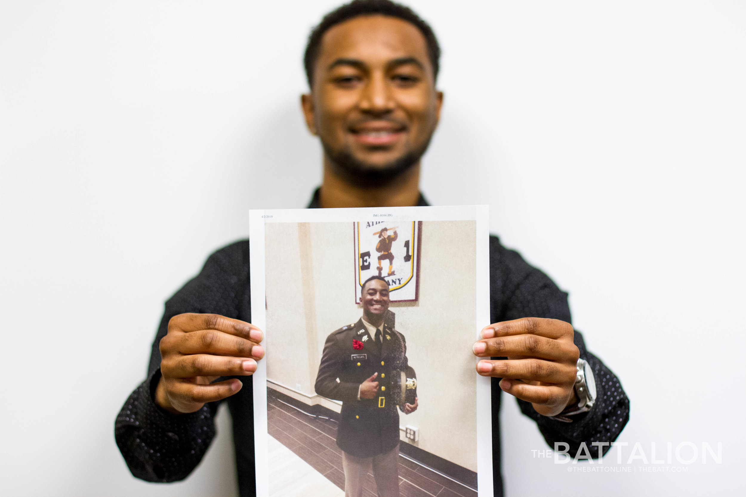 International studies senior  Tenoch Aztecatl  holds up a photo of himself as a cadet.   Photo by Meredith Seaver.