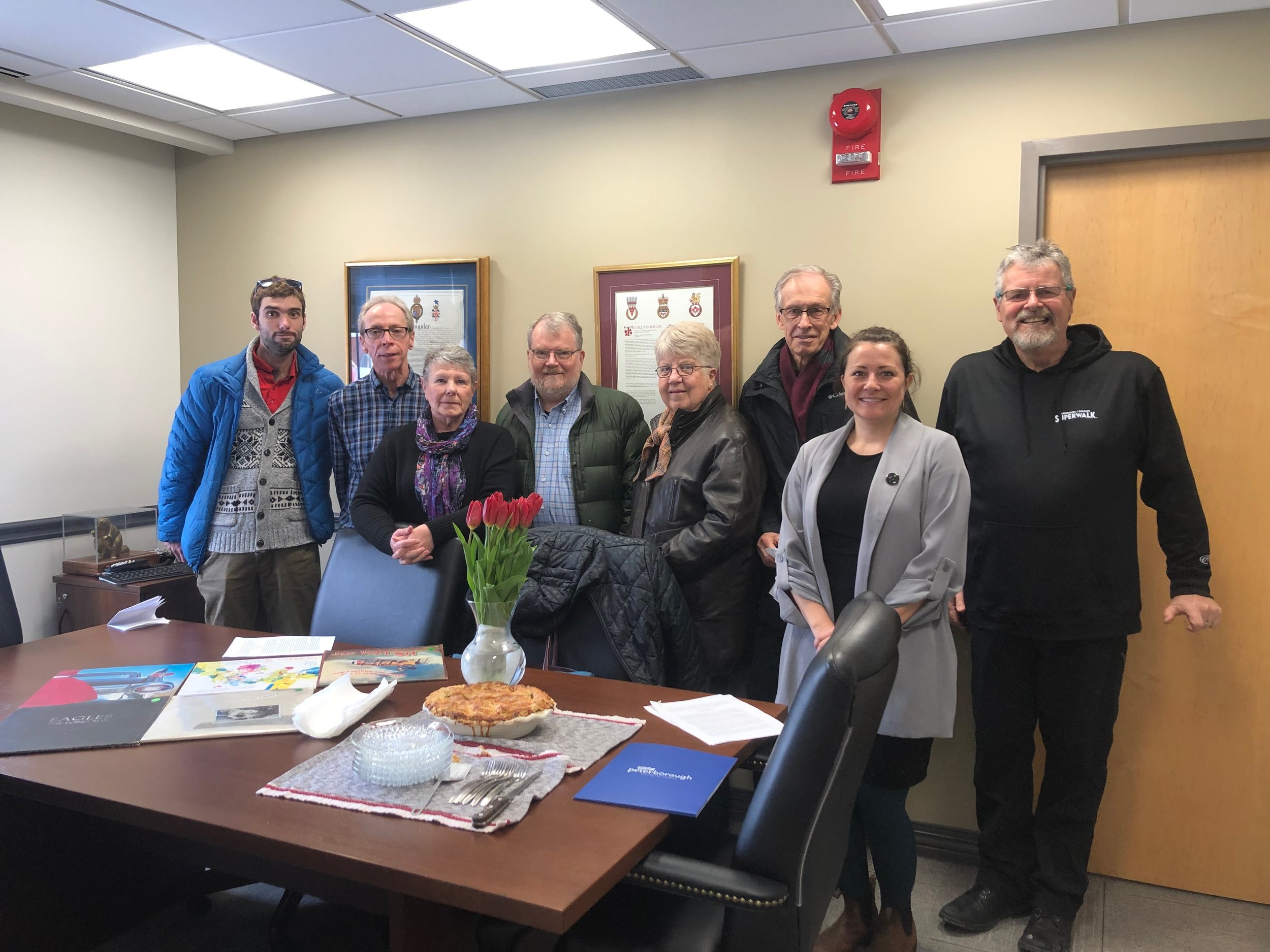 In the mayor's office - On April 2, 2019, a delegation from the Peterborough Parkinson's Chapter witness the Mayor's declartion of April as Parkinson's Awareness Month. Some Albums for the Sale on April 27th event are on the table with tulips as well as Joe's apple pie shared & enjoyed by all.