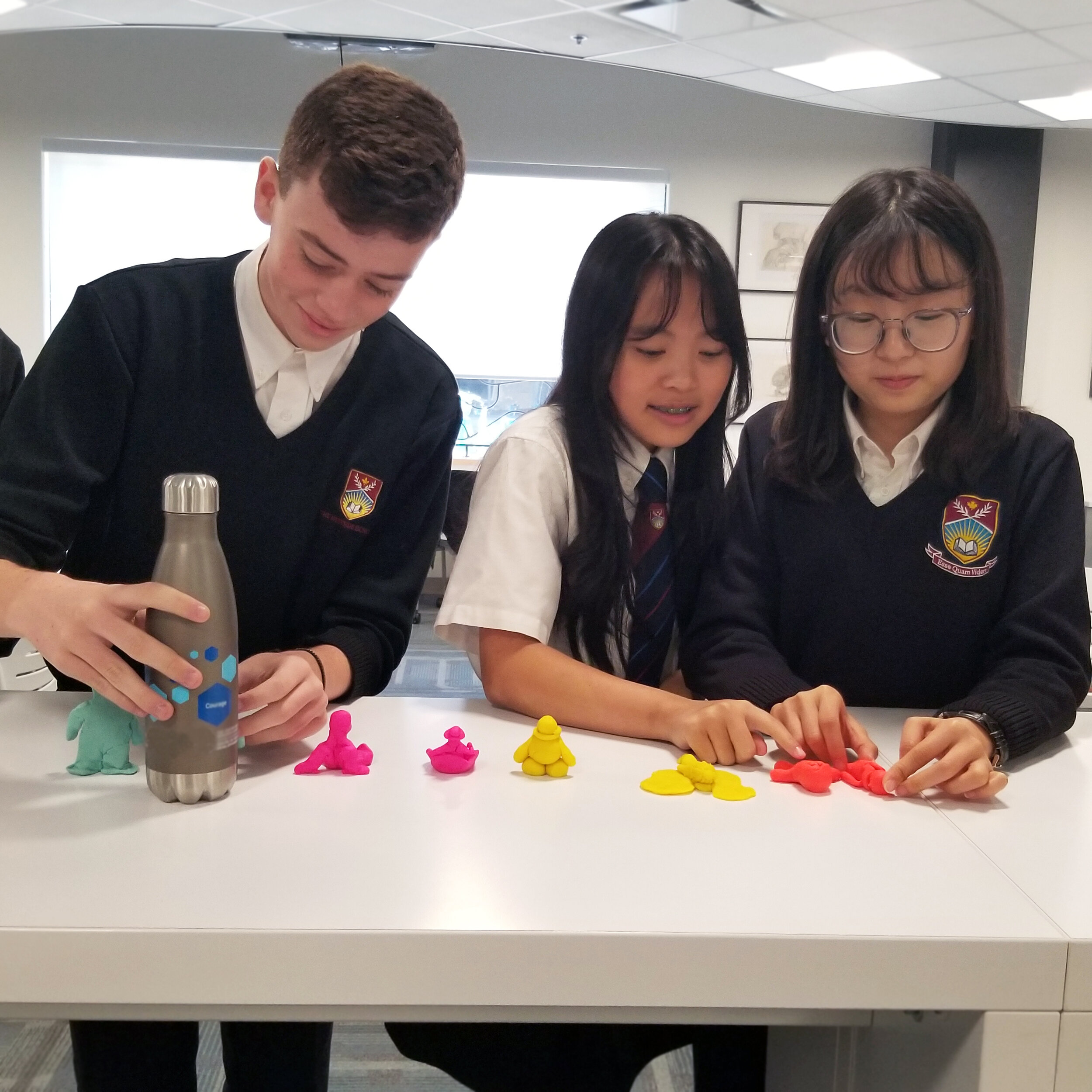 Students are learning about the philosophy of Plato through the creation of human figures made from Play-Doh.