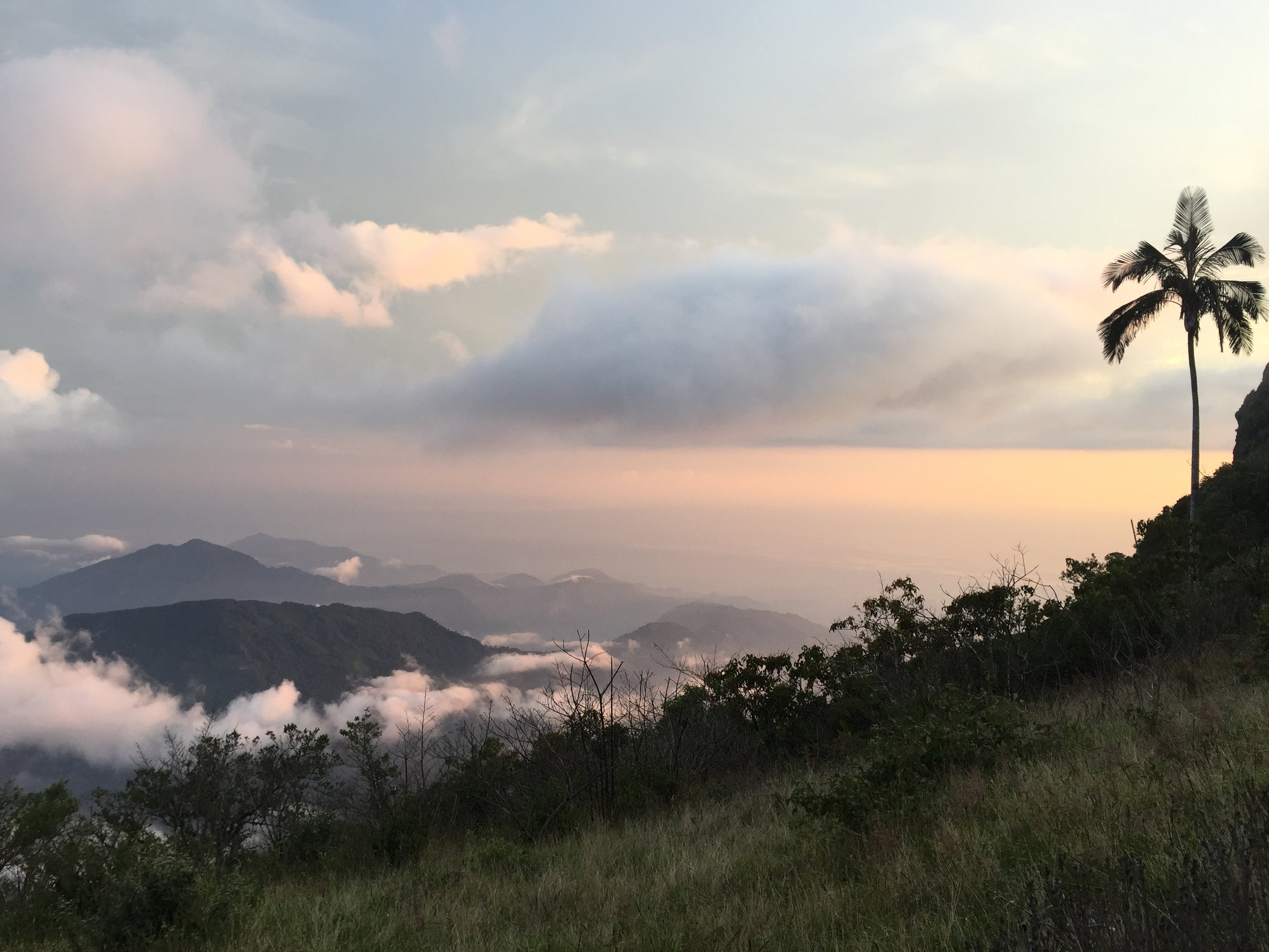 CERRO KENNEDY, COLOMBIA – JULY 28TH, 2017: The view from the summit of Cerro Kennedy, 7000 feet above the town of Minca. Clouds stream down from the lower peaks to the sea, less than 41 miles away.