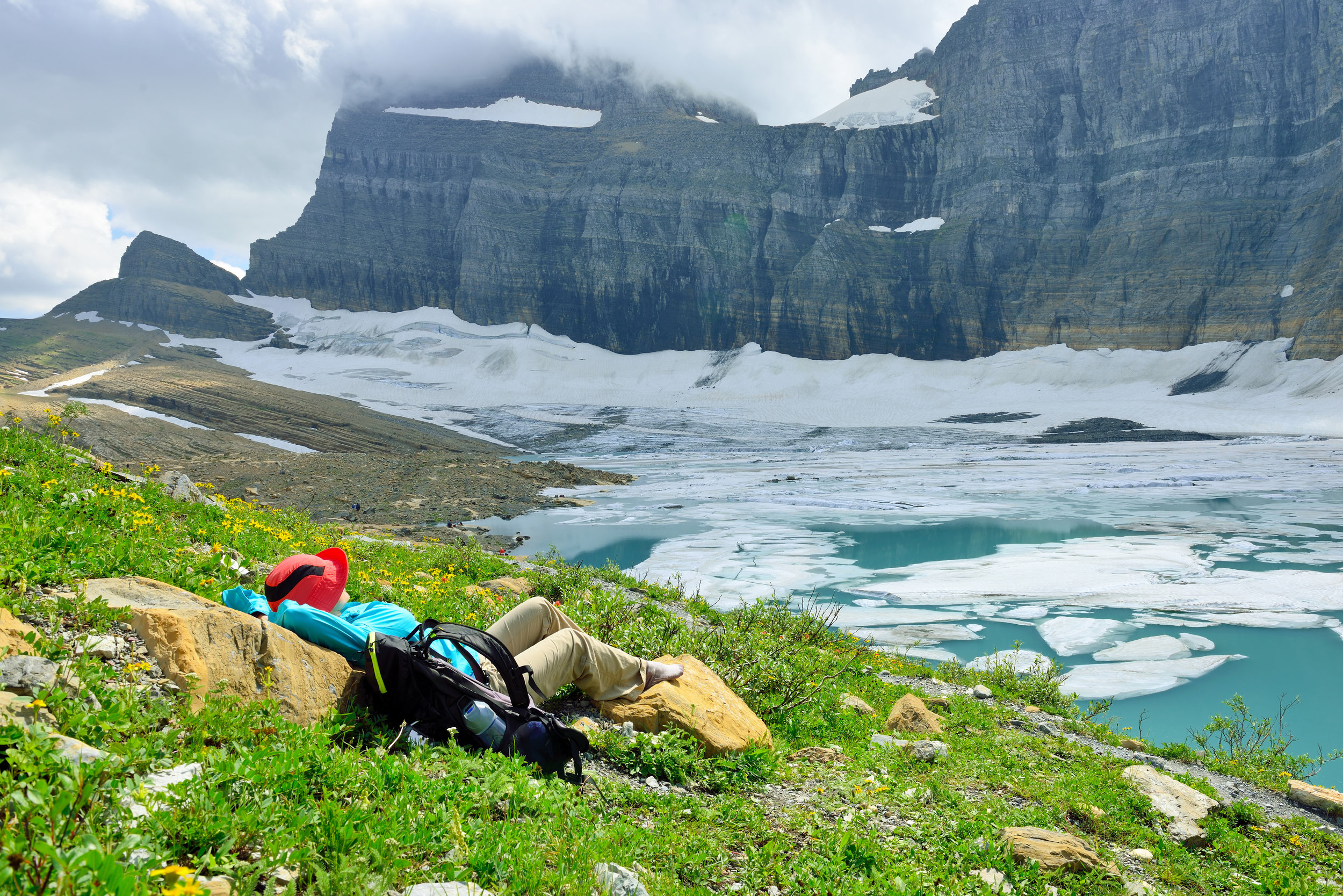 PICTURED:  female hiker resting by the Grinnell glacier in Many Glaciers, Glacier National Park, Montana in summer. North American glaciers are the most at risk, the study suggests.