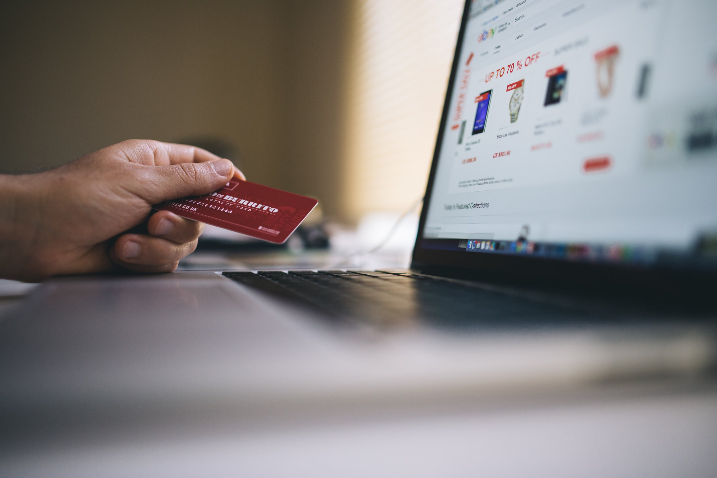 A person holds a physical debit card while shopping online