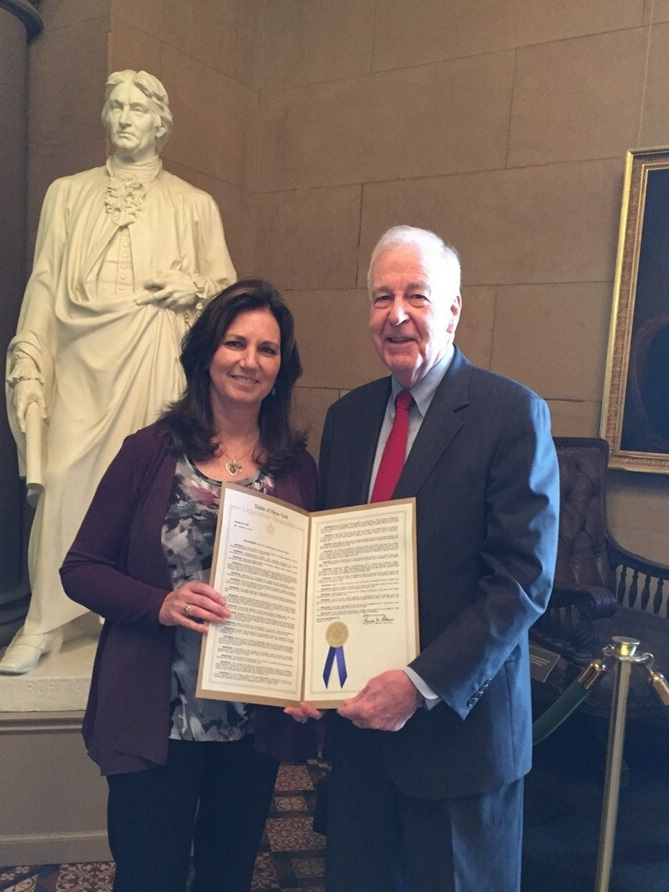 Patti Wukovits and Senator Kemp Hannon of Long Island, NY holding the MenB Awareness Month resolution on June 2018.