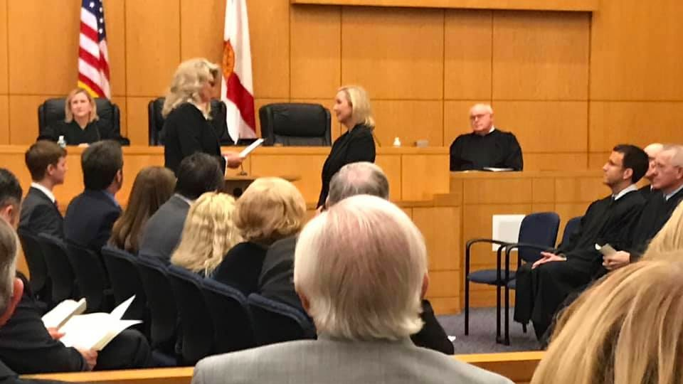 Escambia County Clerk of the Court Pam Childers reads the commission to Judge Lacey Powell Clark. Ms. Childers and Judge Clark are both IWP members.