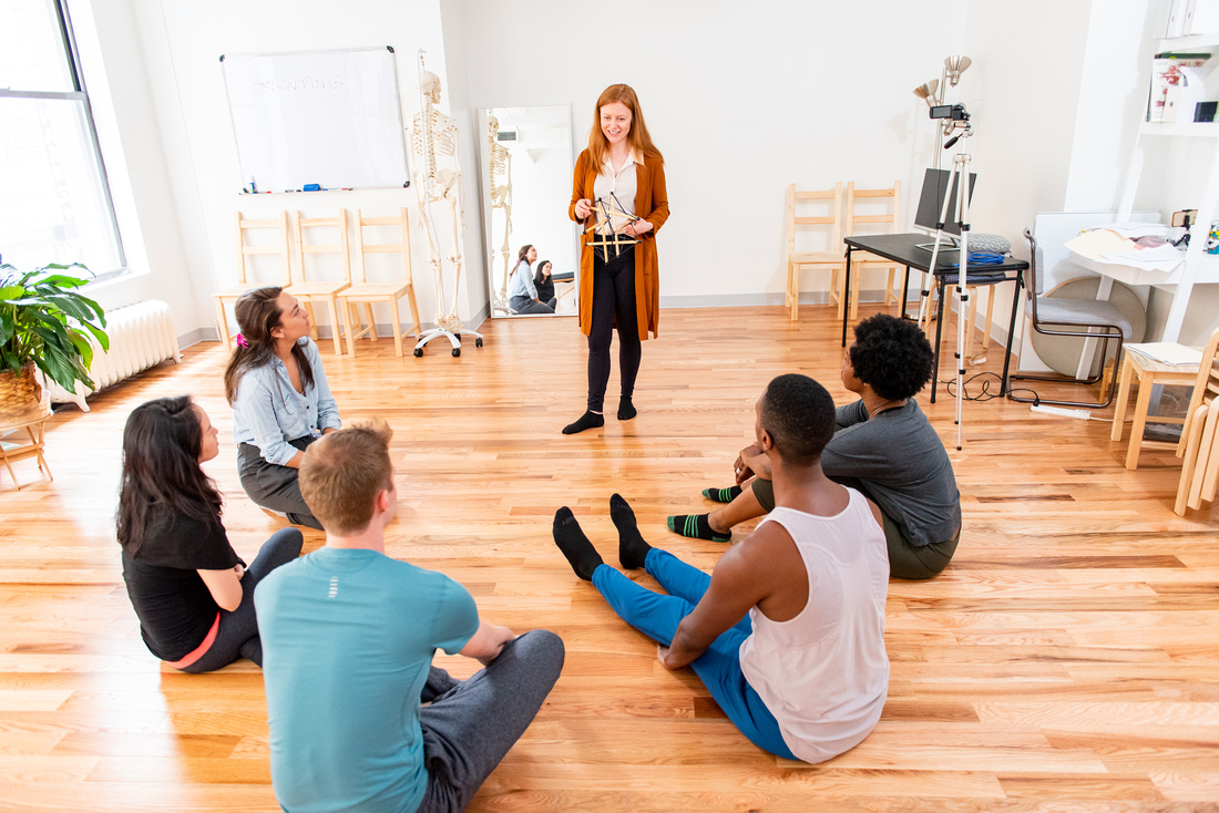 Holly Cinnamon, working actor and Alexander Technique teacher in NYC, stands in front of a class of students who are sitting on the floor. She holds a tensegrity structure as she explains how the use of yourself and your attention can change how you reach an audience in theatre and film. A camera and monitor is set up on a table behind her.