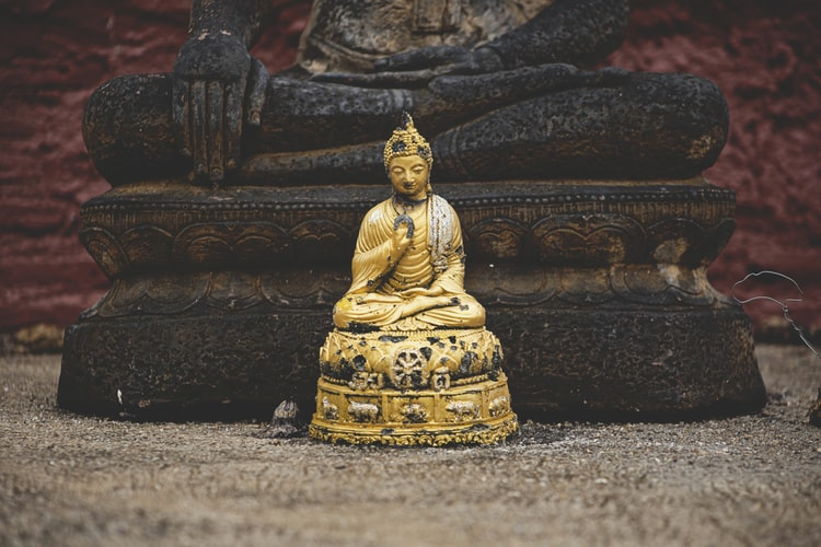 A golden Buddha statue sits on the ground in front of a larger Buddha statue.
