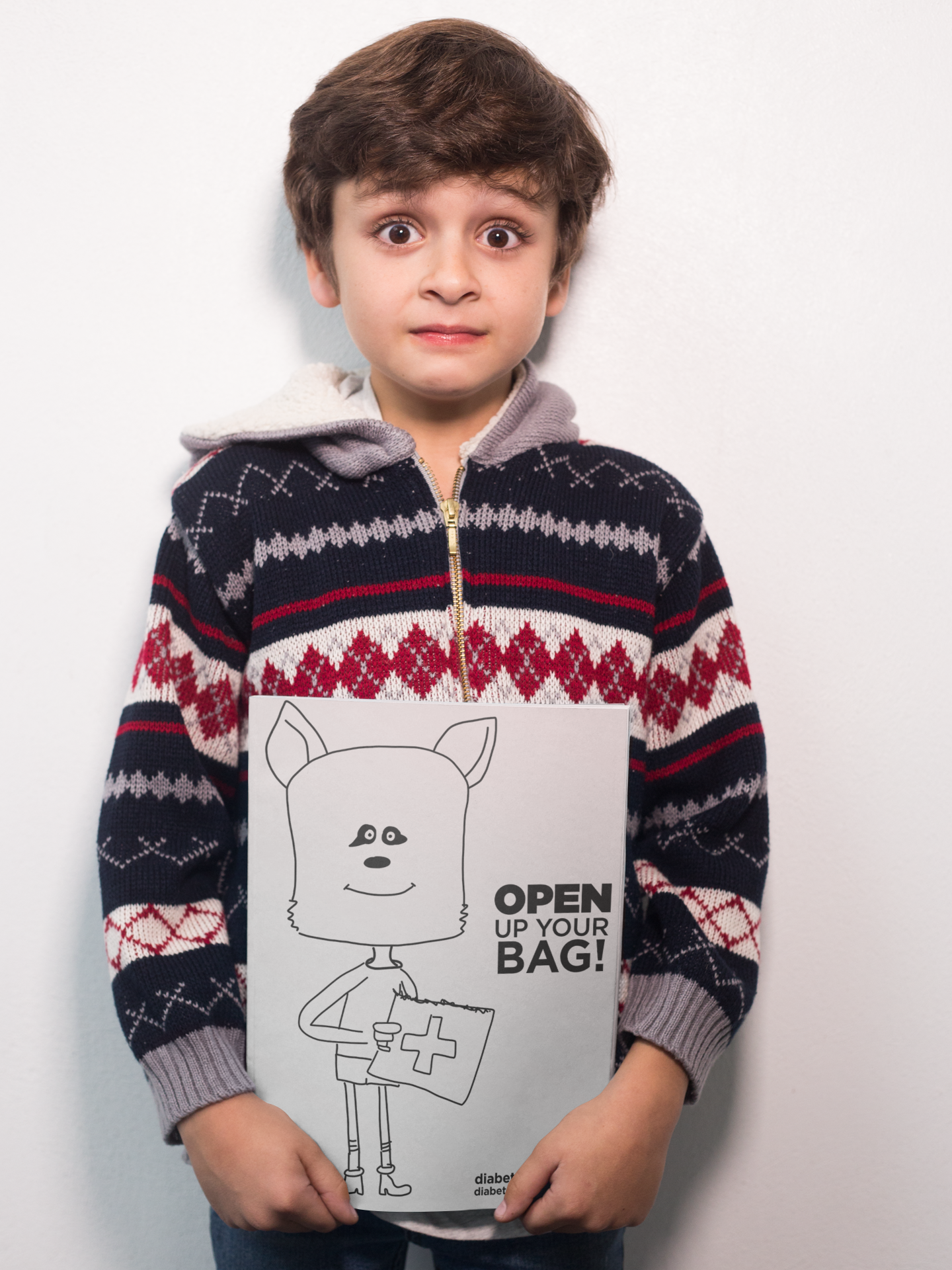 surprised-boy-holding-a-book-mockup-against-a-white-wall-a19219-2.png