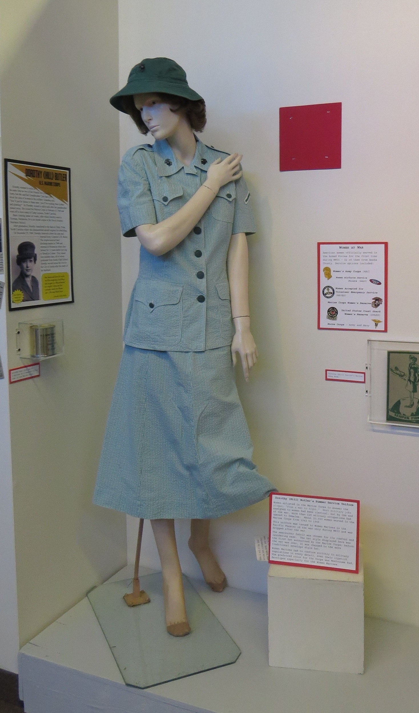 """Dorothy (Hill) Butler's Summer Service Uniform   Women enlisted in the Marine Corps in answer to the slogan, """"Free a man to fight."""" Most military jobs assigned to women had been clerical, but by the end of the war, more than 225 military occupations were open to Women Marines. Some 23,000 women served in the Marine Corps from 1942 to 1946. This uniform was issued to Women Marines in the Pacific Theater of the war only during WWII. This style of uniform was dropped after the war. The seersucker fabric was chosen for its comfort and laundering ease. The hat style here was the first hat authorized by the Marine Corps; it was changed to the more traditional envelope style before the war was over. Women Marines had to conform strictly to military regulations in every detail, even their lipstick. The preferred color for the Corps was Montezuma Red, developed especially for the Women Marines."""