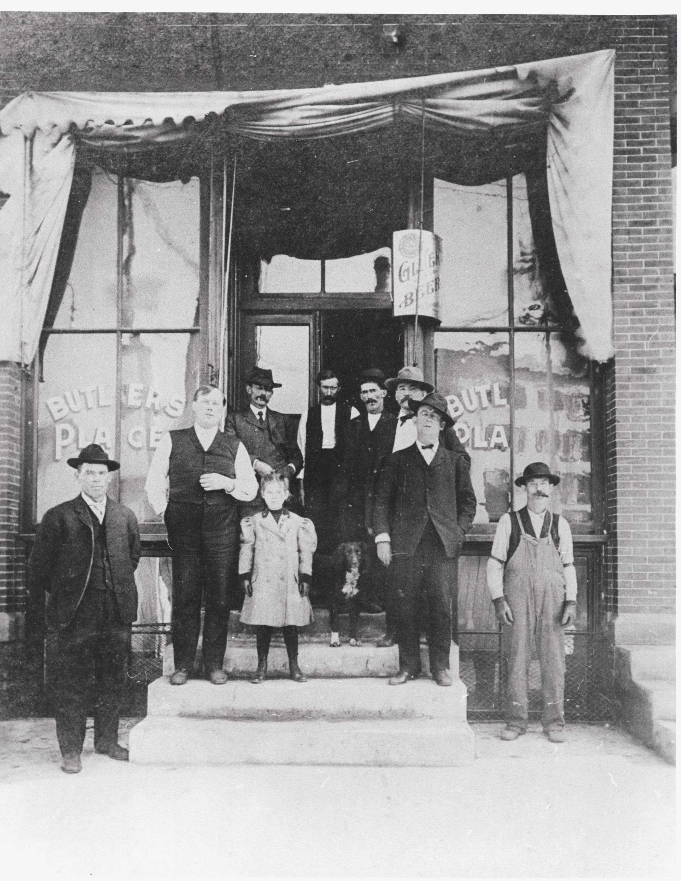 Doorway of the Farmers' Hotel saloon, called Butlers Place, sometime after 1906 (dated because the concrete sidewalks seen in this photograph were installed that year). The second man from the left, standing on the stairs in shirtsleeves, is identified as Edward H. Butler, nephew of the owners. (Object ID# 2057.3.46)