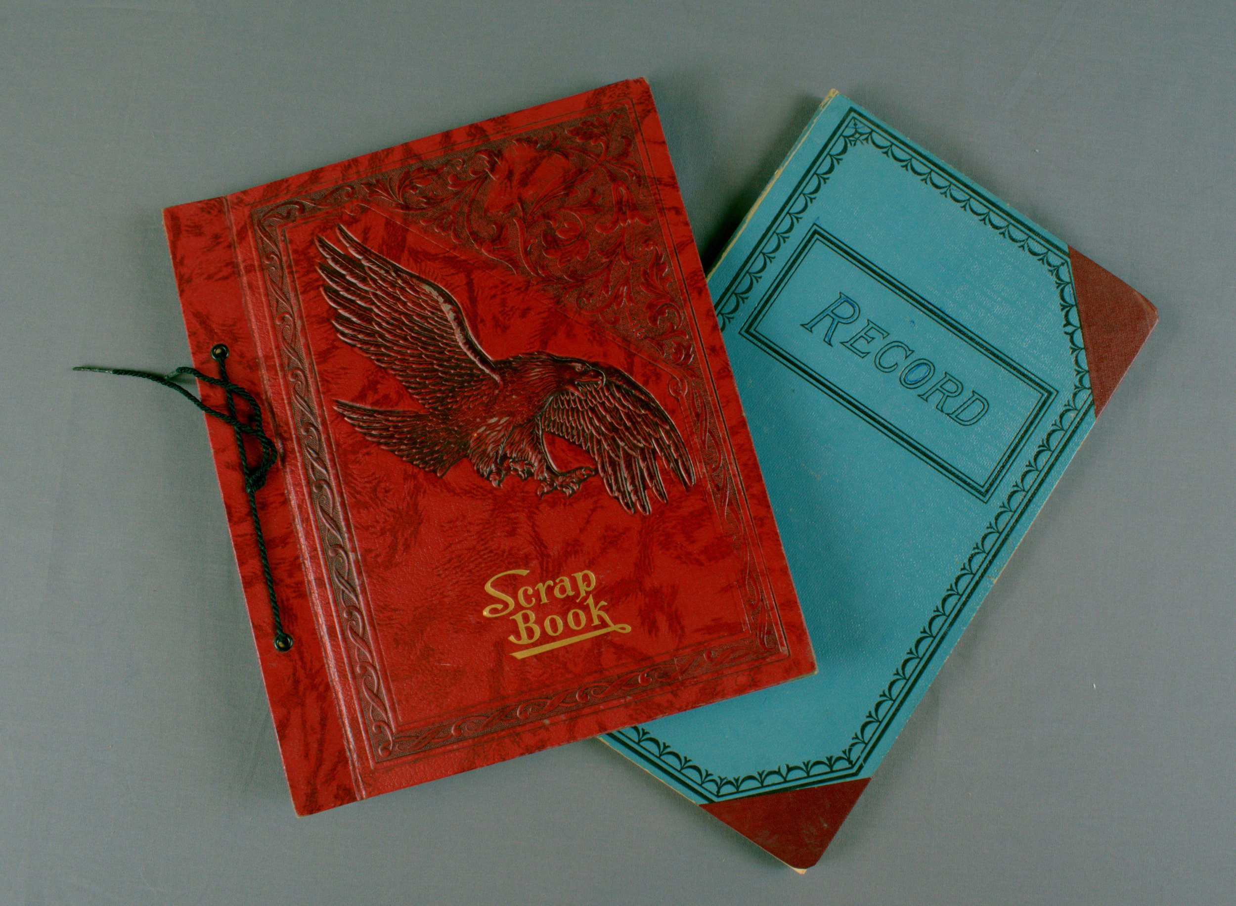 "This 9 1/4 x 11"" scrapbook has a red cover with an embossed eagle in center and gold lettering ""Scrap Book"" on front cover. The spine is bound with a black cord tie. The scrapbook contains newspaper articles written by O.H. Prestemon between 1940-1951 on flowers and Columbia Heights Garden Club notes.  This 12 x 7 1/2"" blue hard cover ledger has burgundy corners. The inside cover has a handwritten note indicating the book contains the minutes from 1964-1966 and the official record of the Columbia Heights Garden Club."