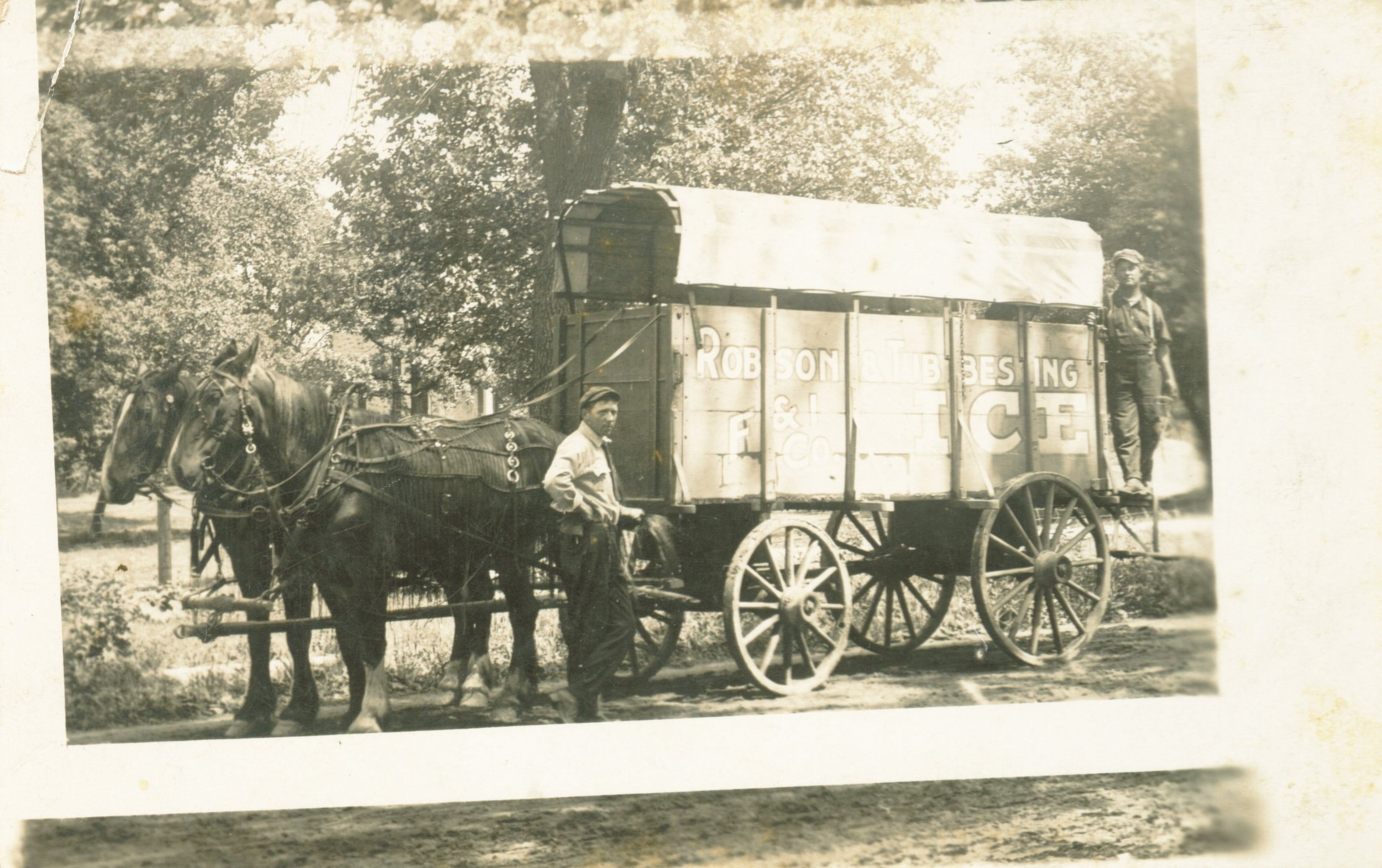 """This is a photo of two horses pulling an ice wagon, which is mounted on four wooden wheels. One man is standing near the front of the wagon, and another standing on a back platform. The sign on the side reads """"Robson & Tubbesing ICE. F & I Co."""" (object ID 2507P.16.2.28; from the Jeanette Magnuson Photo Collection)."""