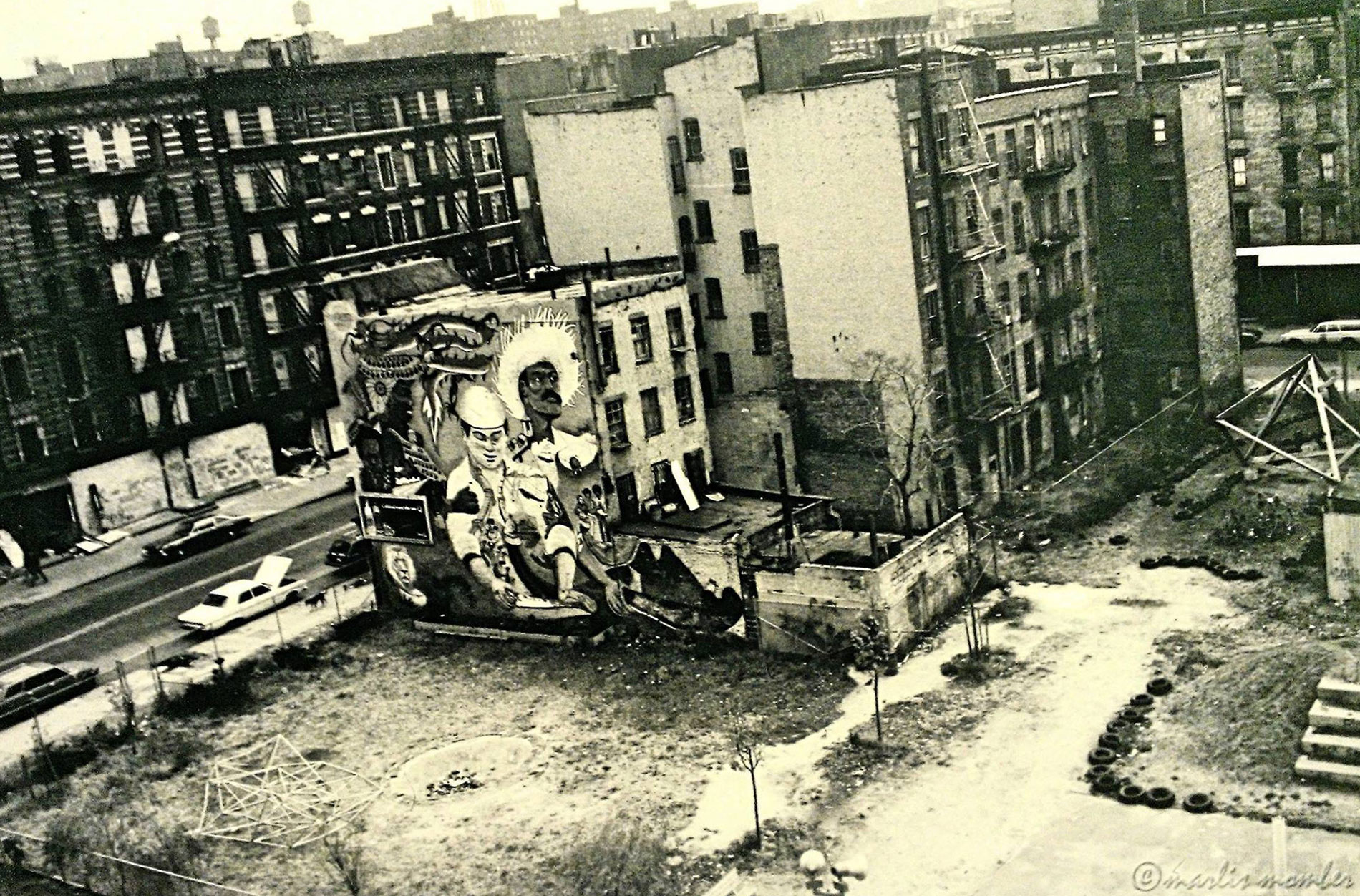 La Plaza Cultural, circa 1980, when Freddy Hernandez's 1977  La Plaza Cultural Mural  overlooked the community garden. Due to wall leaks, the mural was tarred over, replaced in 1985 by La Lucha's collective mural.   Photo © Marlis Momber