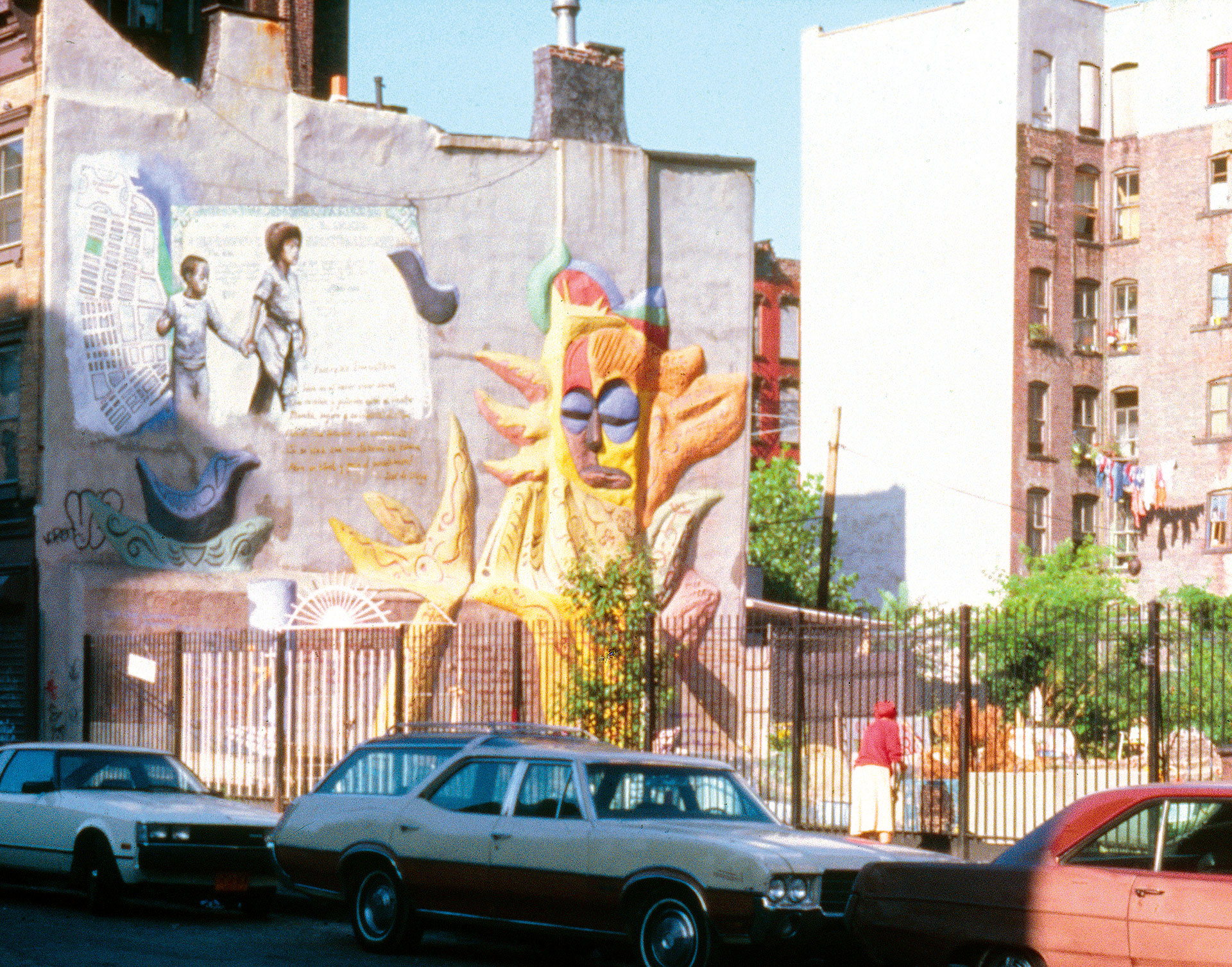 'From One Generation to Another The Struggle Continues , John Pitman Weber, 1984, Cityarts Workshop, 1984.  The mural overlooks El Jardín Bello Amanecer Borinqueño, created by community juror Carmen Pabón (in front of garden gate).  Photo: source unknown