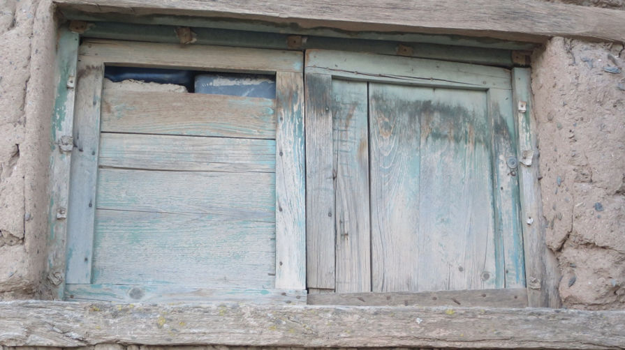Shutters of faded blue on an abandoned adobe house.